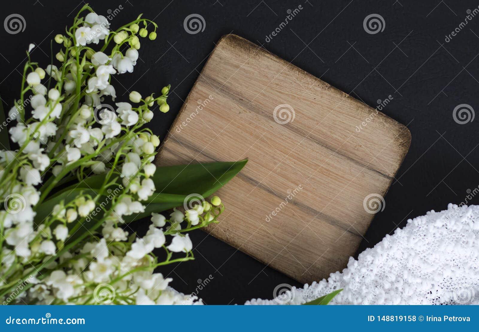 Ο άσπρος κρίνος της κοιλάδας ανθίζει στο μαύρο υπόβαθρο με τον ξύλινο πίνακα στο διαστημικό και λεπτό ύφασμα αντιγράφων