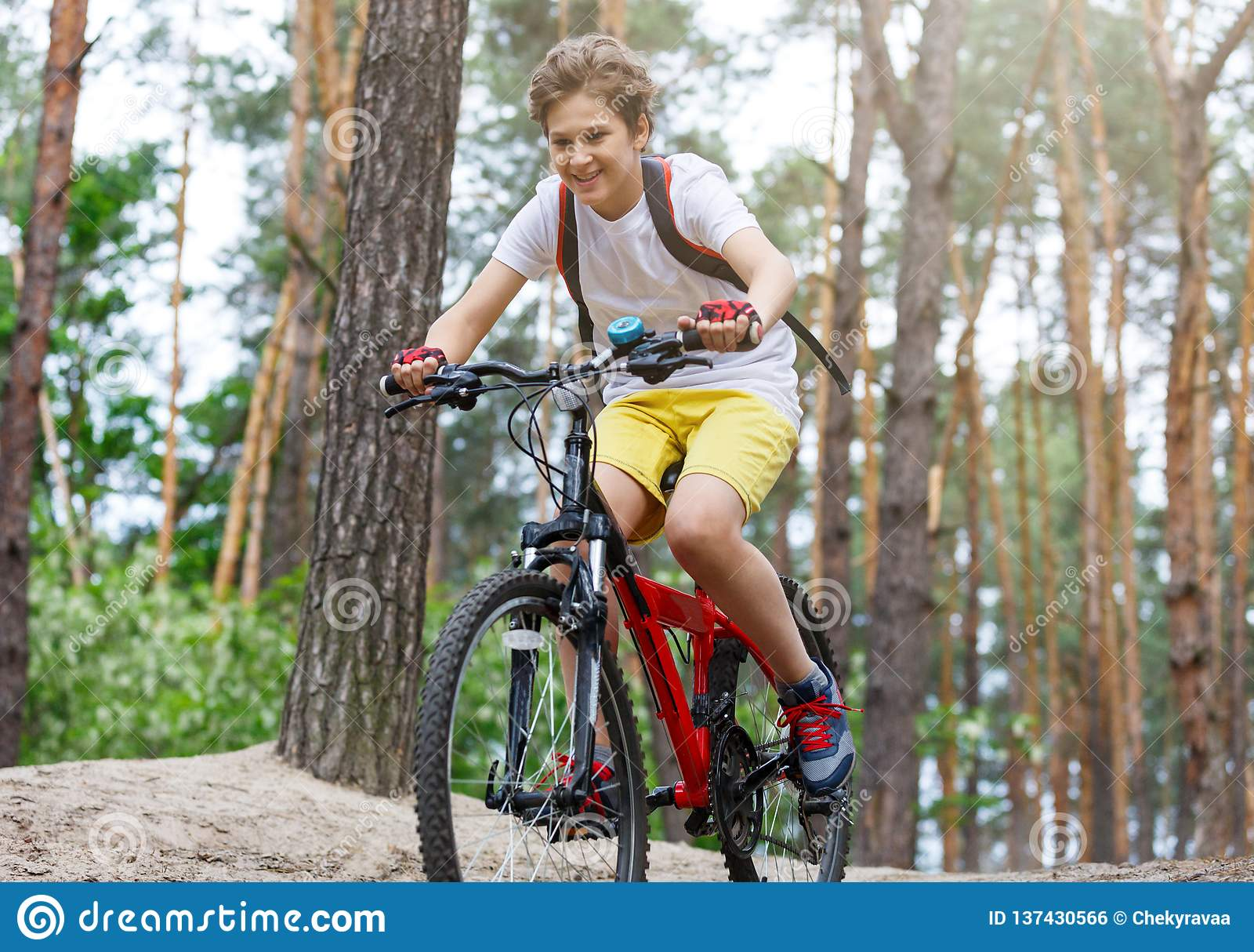 Ο έφηβος παιδιών στην άσπρη μπλούζα και τα κίτρινα σορτς στο ποδήλατο οδηγούν στο δάσος στην άνοιξη ή το καλοκαίρι Ευτυχής ανακύκ