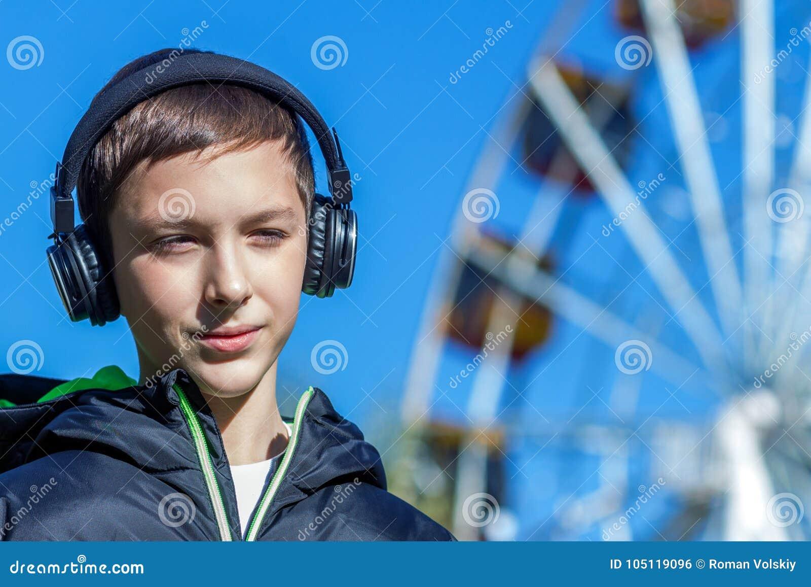 Ο έφηβος σε ένα μαύρο σακάκι, που ακούει τη μουσική με τα ακουστικά κοντά στη ρόδα Ferris διασκέδασης