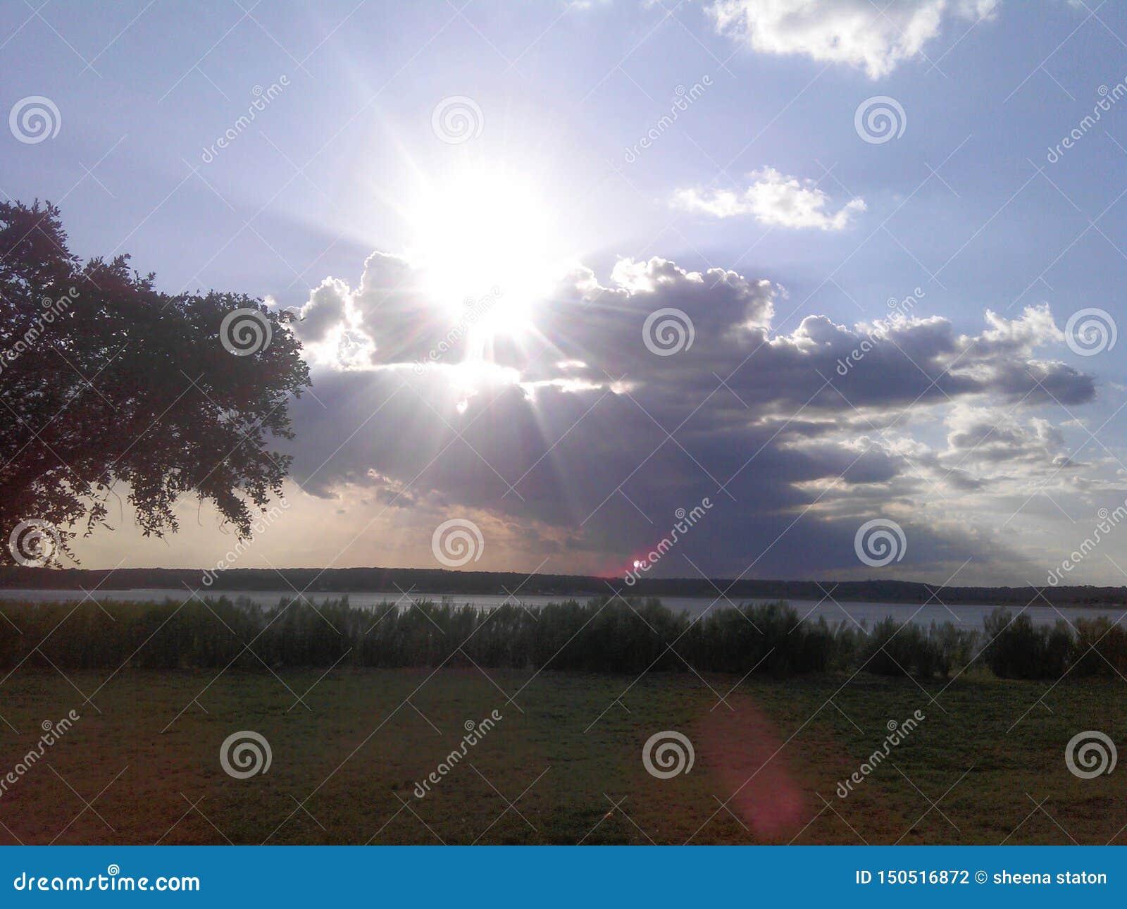 Ο ήλιος που κρύβει πίσω από τα σύννεφα πέρα από μια τεξανή λίμνη