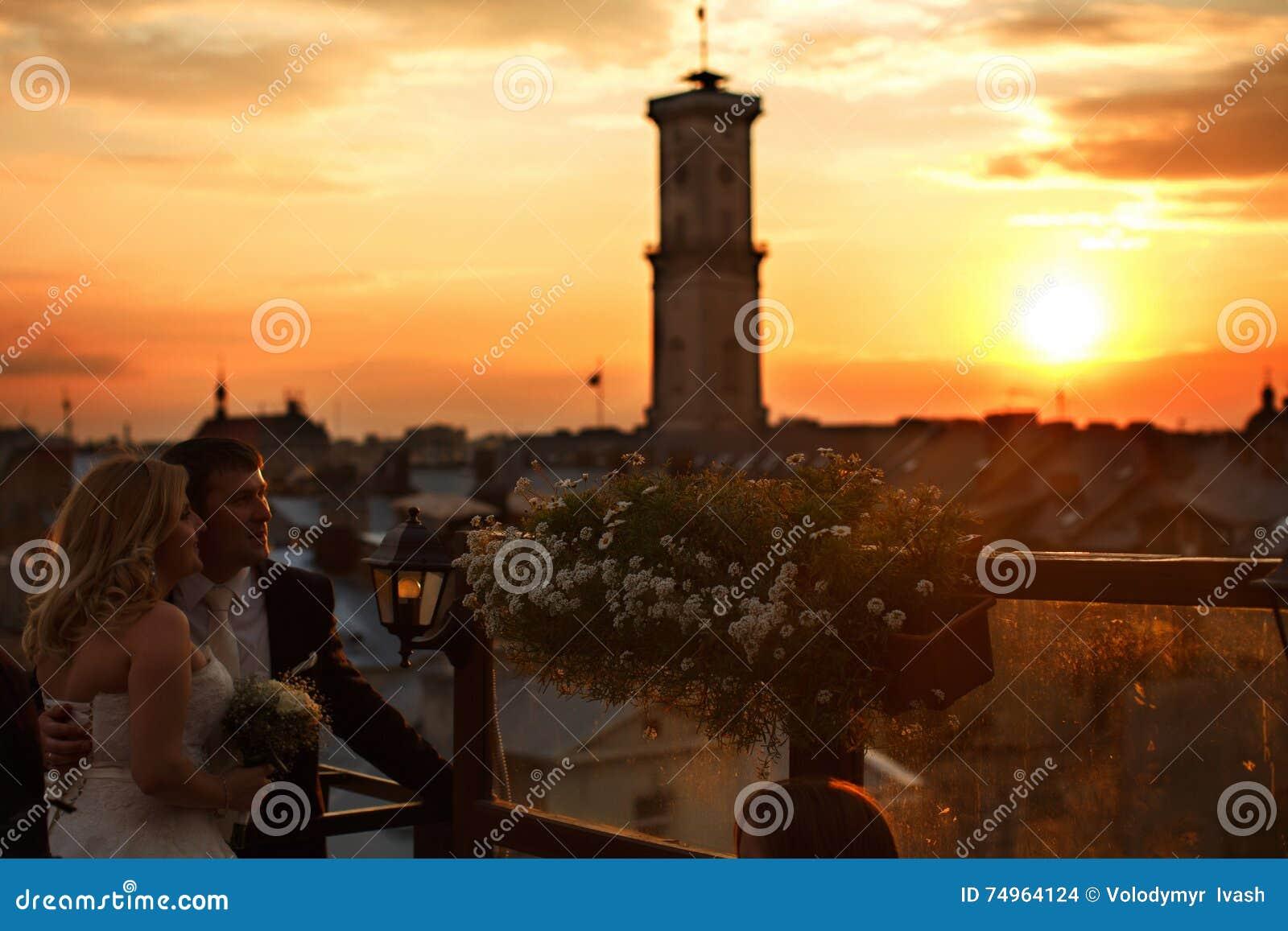 Ο ήλιος πέρα από μια παλαιά πόλη ενώ νύφη και νεόνυμφος tal