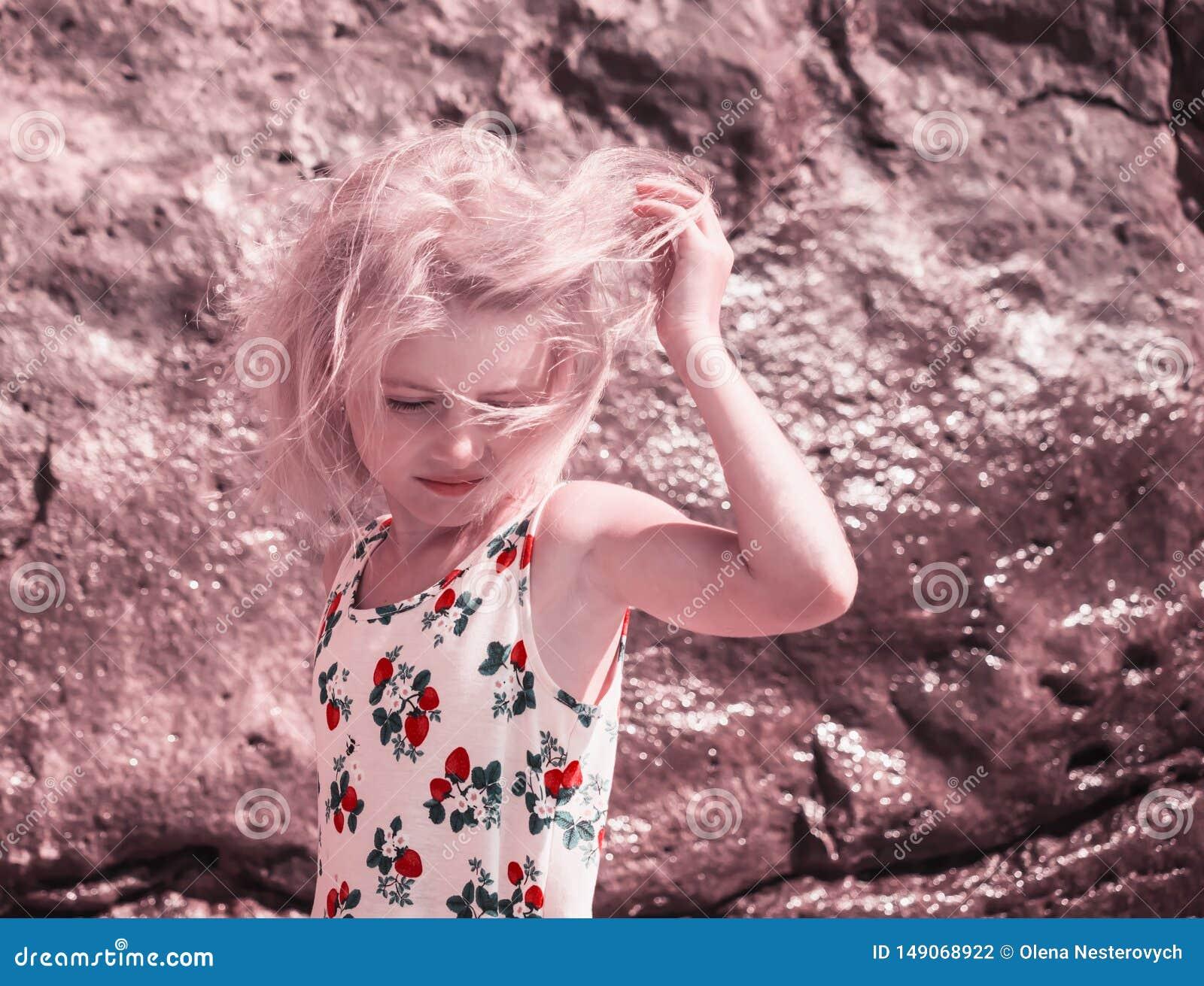 Ο αέρας παίζει την τρίχα στο ξανθό κορίτσι στην παραλία