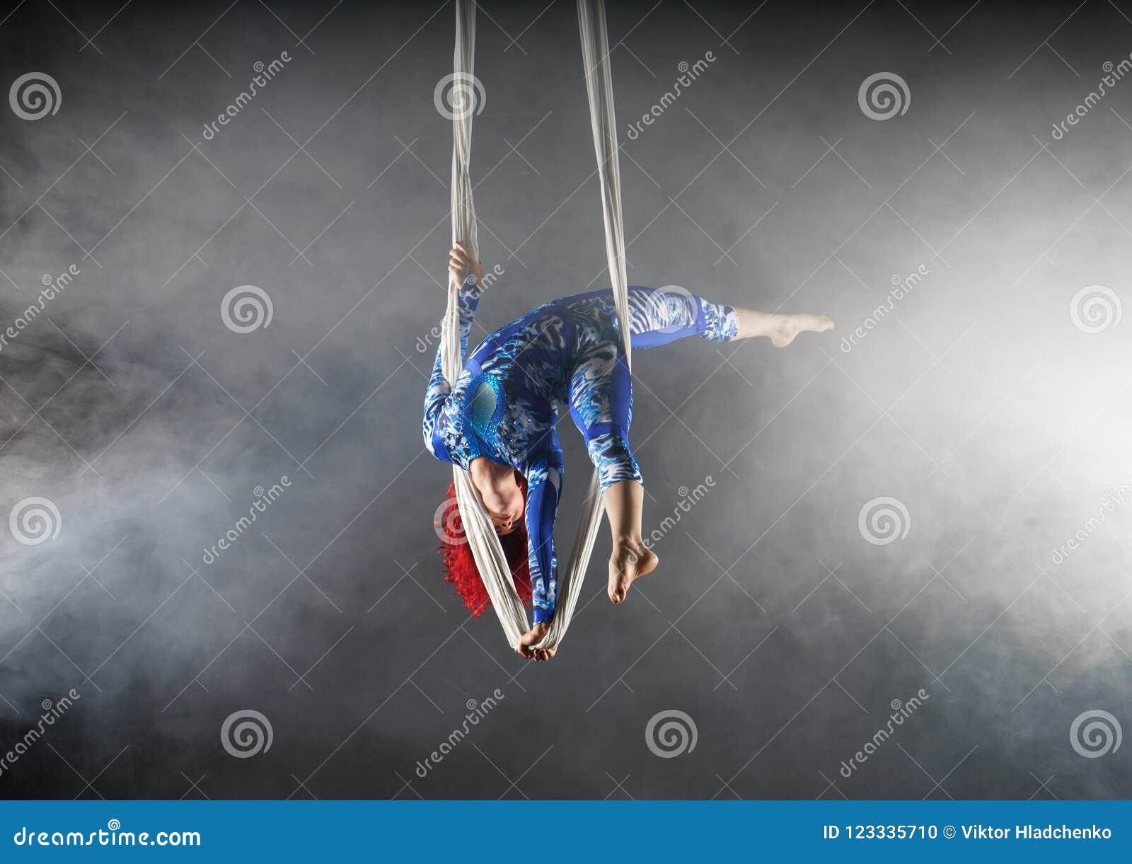 Ο αθλητικός εναέριος καλλιτέχνης τσίρκων με redhead στο μπλε κοστούμι που στέκεται στο ένα παραδίδει το εναέριο μετάξι