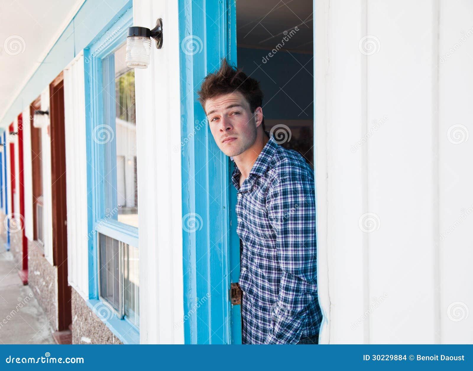 Ο νεαρός άνδρας κοιτάζει από το δωμάτιο μοτέλ