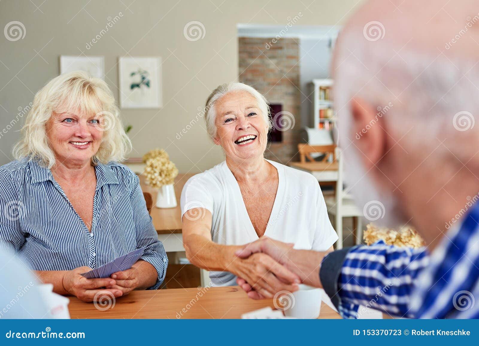 Ο ανώτερος άνδρας καλωσορίζει την ανώτερη γυναίκα με τη χειραψία