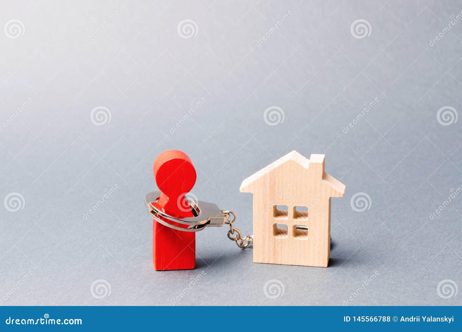 Ο αριθμός ενός ατόμου δένεται με χειροπέδες σε ένα ξύλινο σπίτι Αδύνατο τα επιτόκια στις υποθήκες και την επιστροφή των δανείων