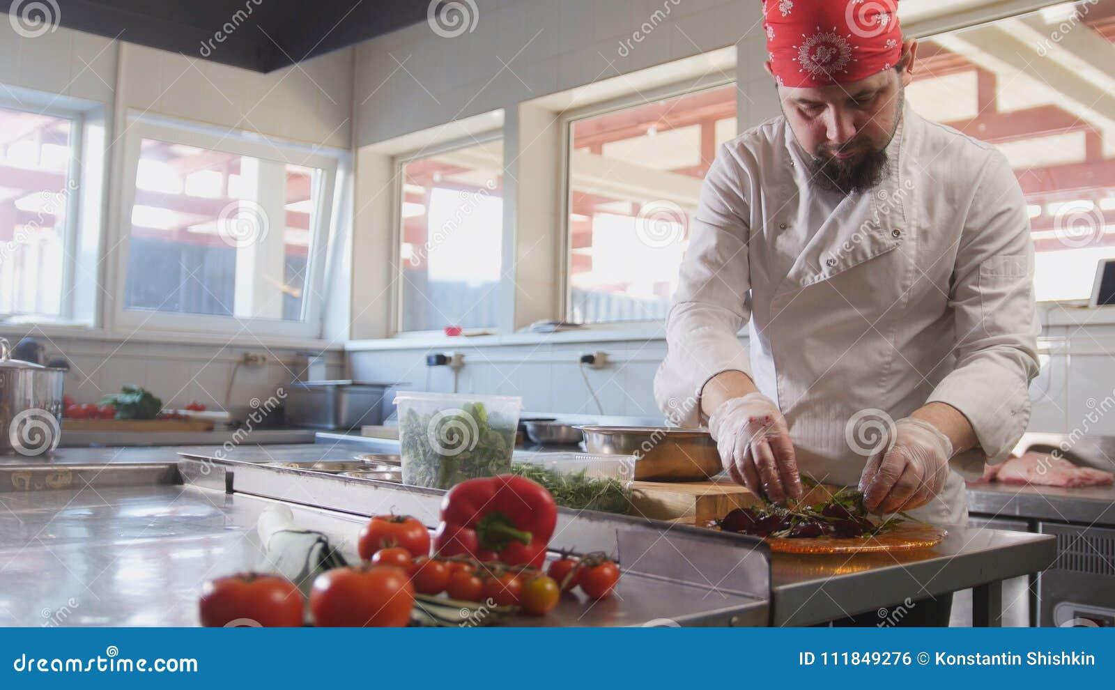 Ο αρχιμάγειρας εξυπηρετεί τη σαλάτα με την τοποθέτηση των συστατικών σε ένα πιάτο