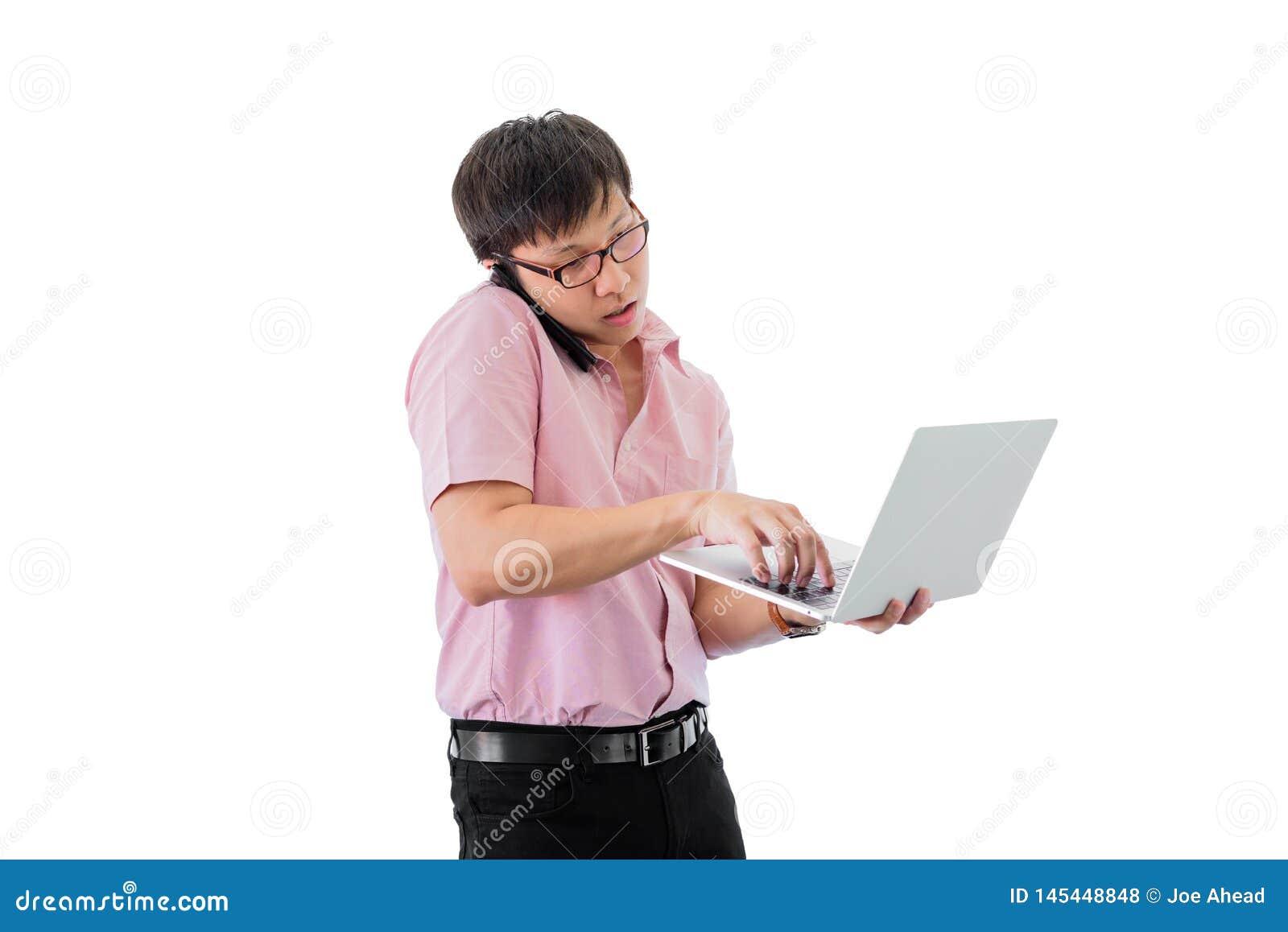 Ο ασιατικός νέος επιχειρηματίας έχει τη στάση και το κράτημα του τηλεφώνου και του lap-top για την εργασία με πολυάσχολο απομονωμ