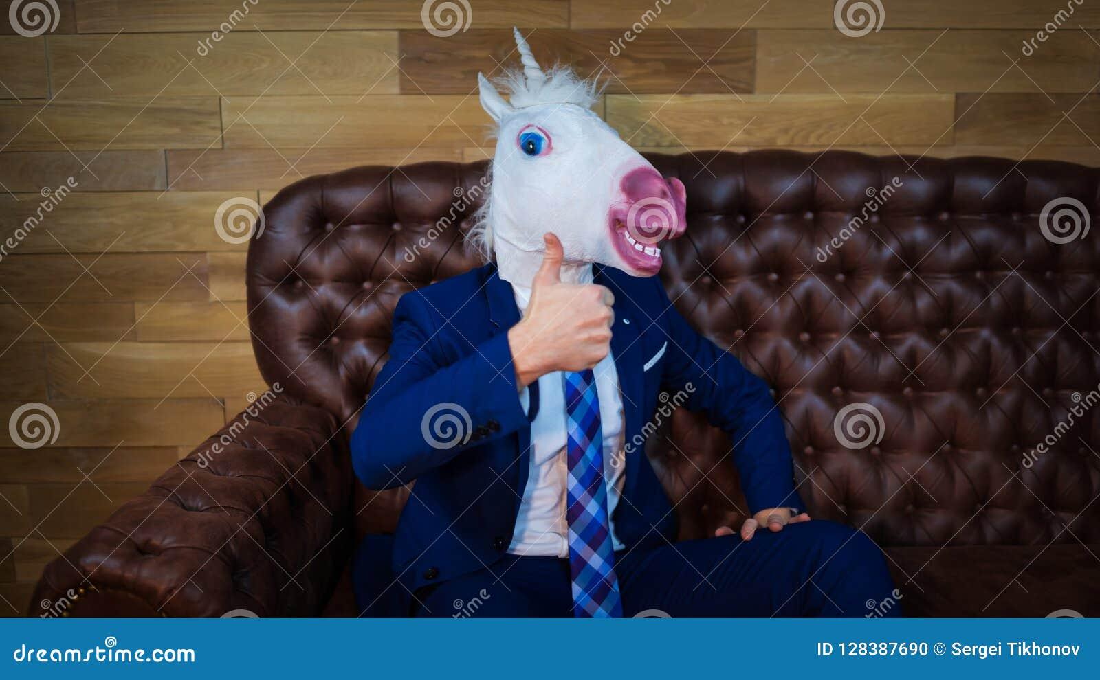 Ο αστείος μονόκερος στο κομψό κοστούμι κάθεται στον καναπέ όπως έναν προϊστάμενο και την παρουσίαση χειρονομίας