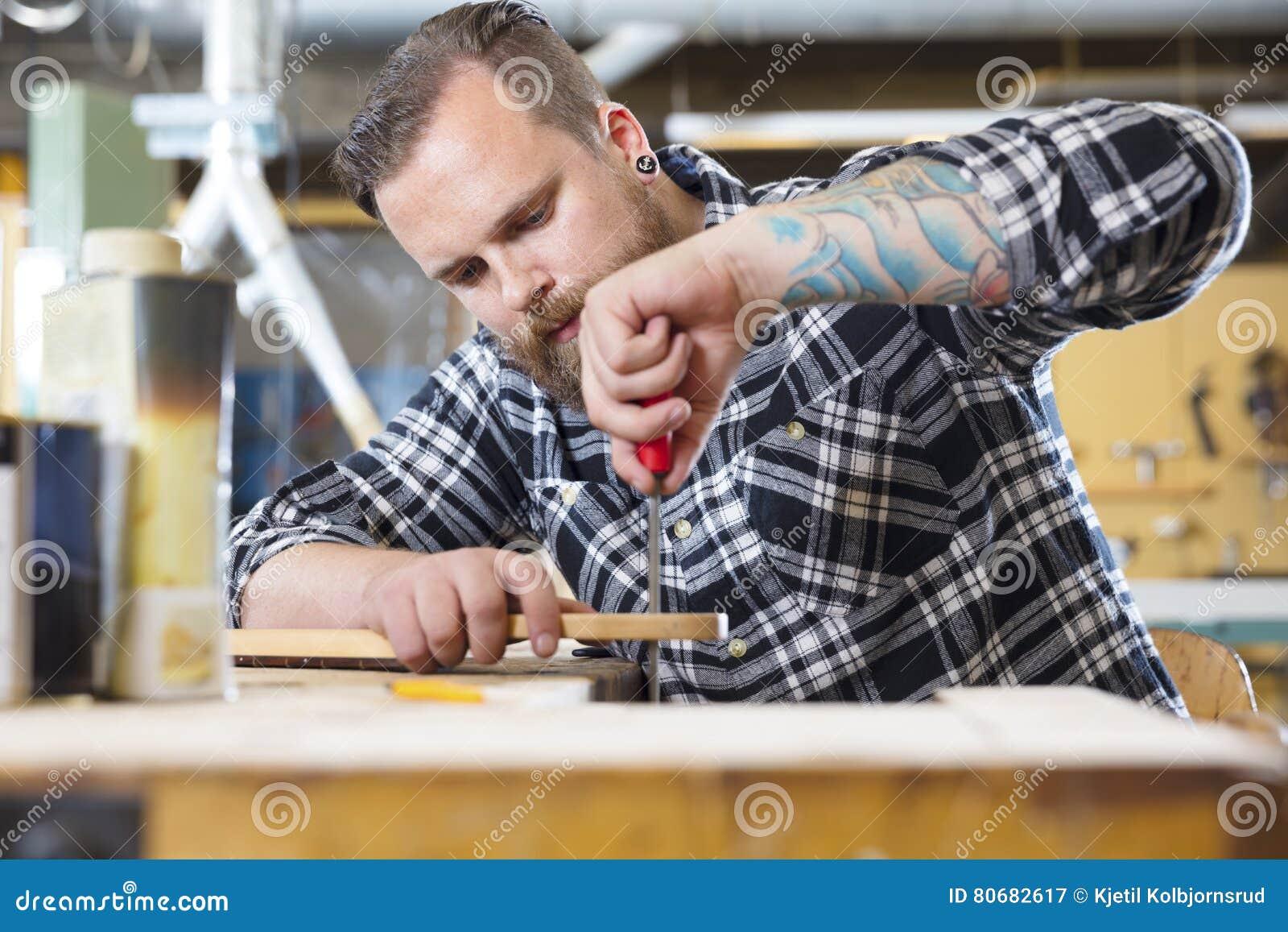 Ο βιοτέχνης αρχειοθετεί τον ξύλινο λαιμό κιθάρων στο εργαστήριο