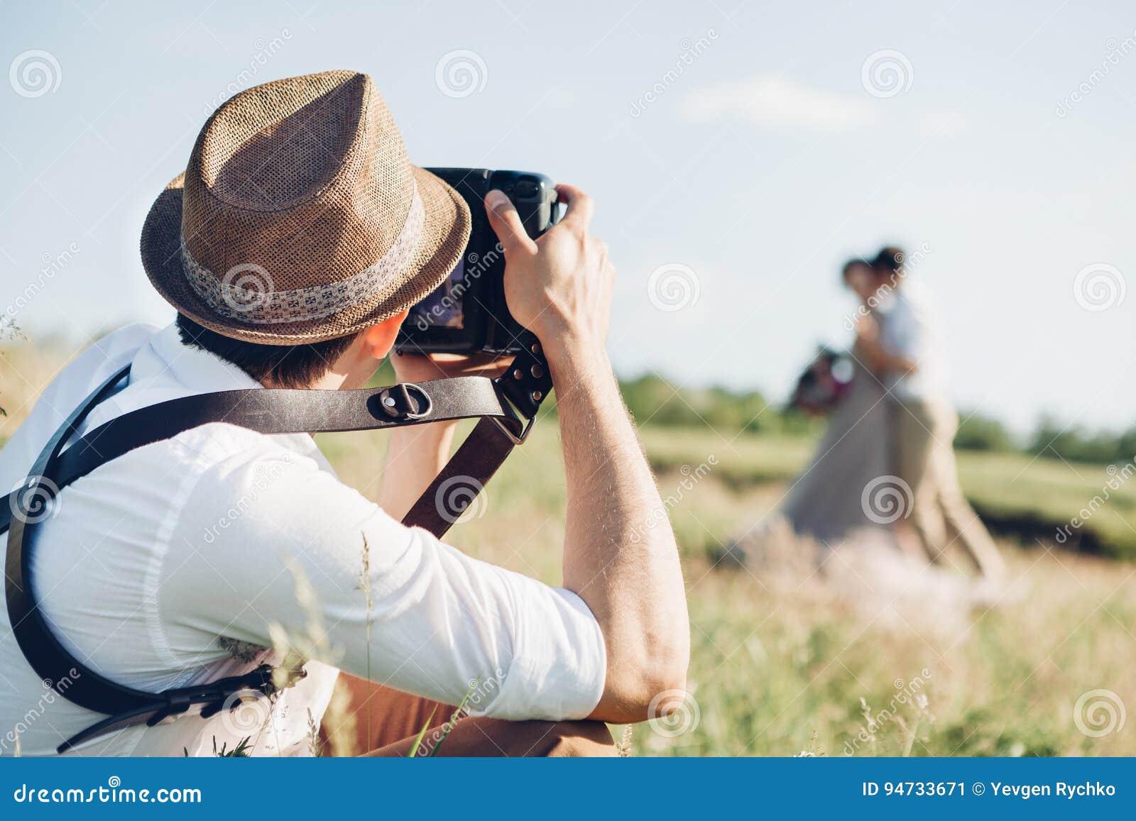 Ο γαμήλιος φωτογράφος παίρνει τις εικόνες της νύφης και του νεόνυμφου στη φύση, φωτογραφία Καλών Τεχνών
