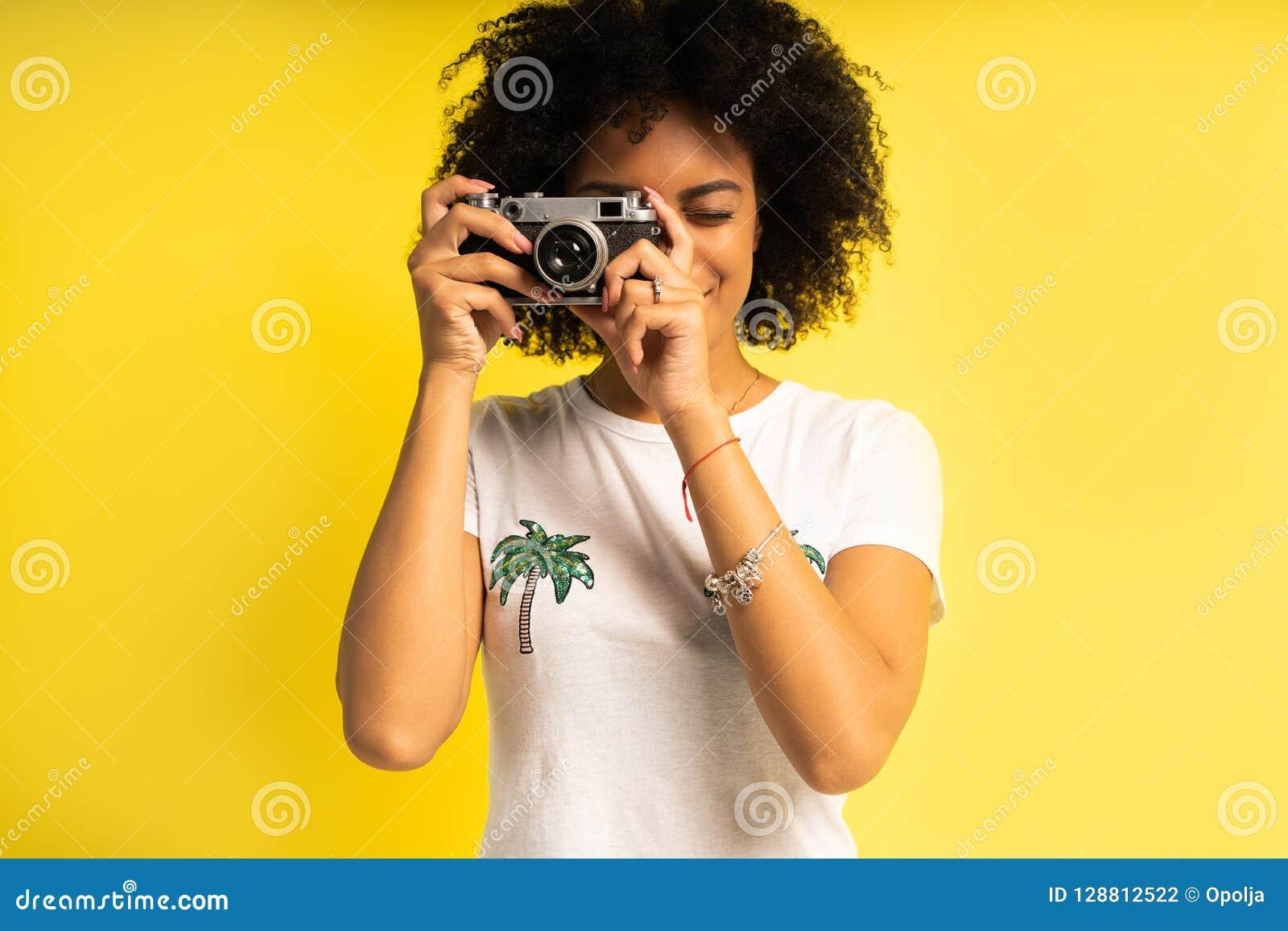Ο δημιουργικός γυναίκα-φωτογράφος παίρνει τις φωτογραφίες, που απομονώνονται σε κίτρινο