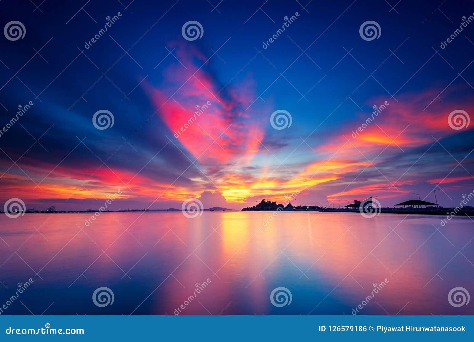 Ο δραματικός πορτοκαλής και ρόδινος σωρείτης καλύπτει στο ηλιοβασίλεμα με το μπλε ουρανό πέρα από το νησί με την ήρεμη και επίπεδ
