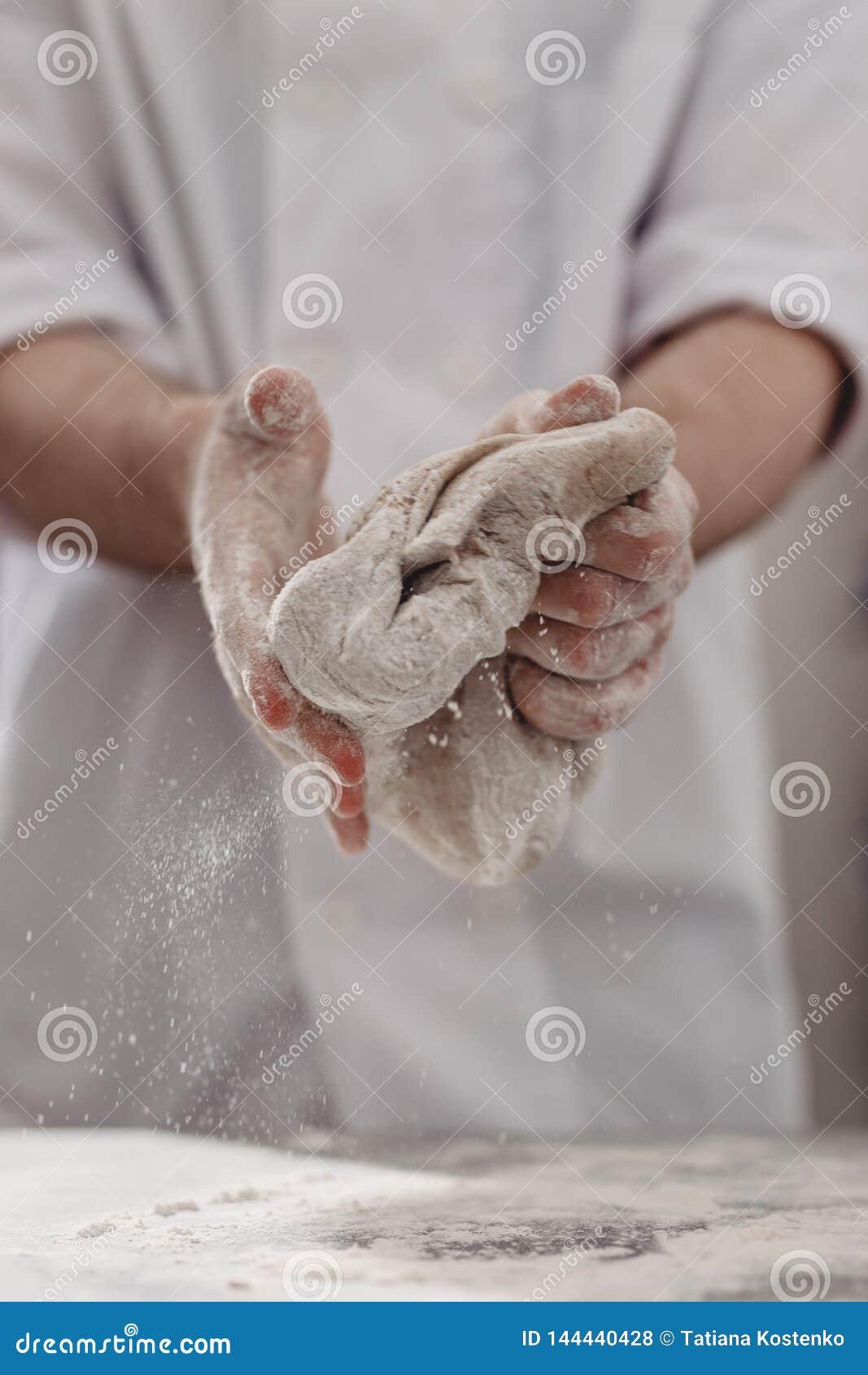 Ο επαγγελματικός αρτοποιός ζυμώνει τη ζύμη σε δικοί του παραδίδει την κουζίνα του αρτοποιείου