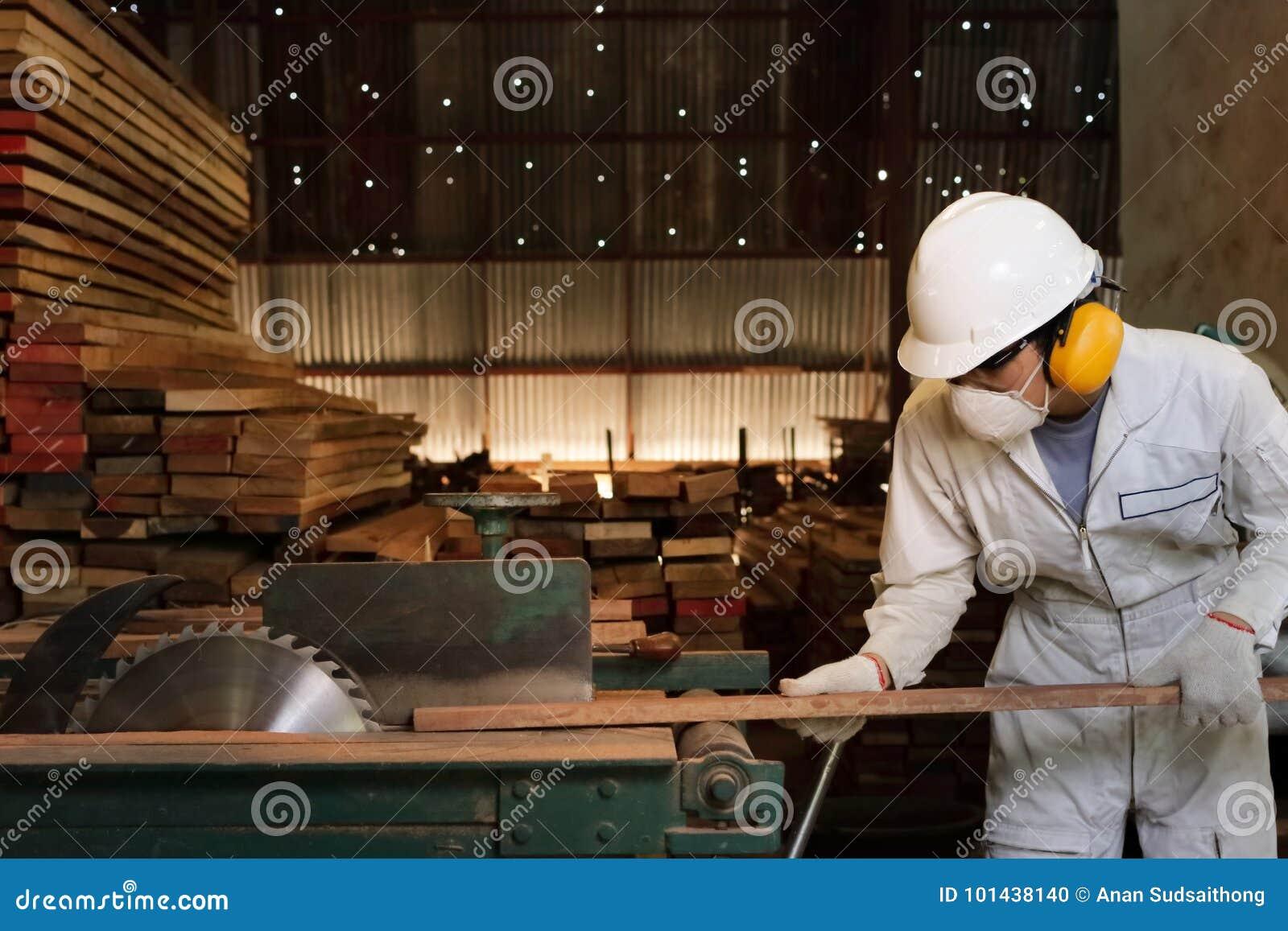 Ο επαγγελματικός νέος εργαζόμενος στον άσπρο ομοιόμορφο και εξοπλισμό ασφάλειας που κόβει ένα κομμάτι του ξύλου στον πίνακα είδε