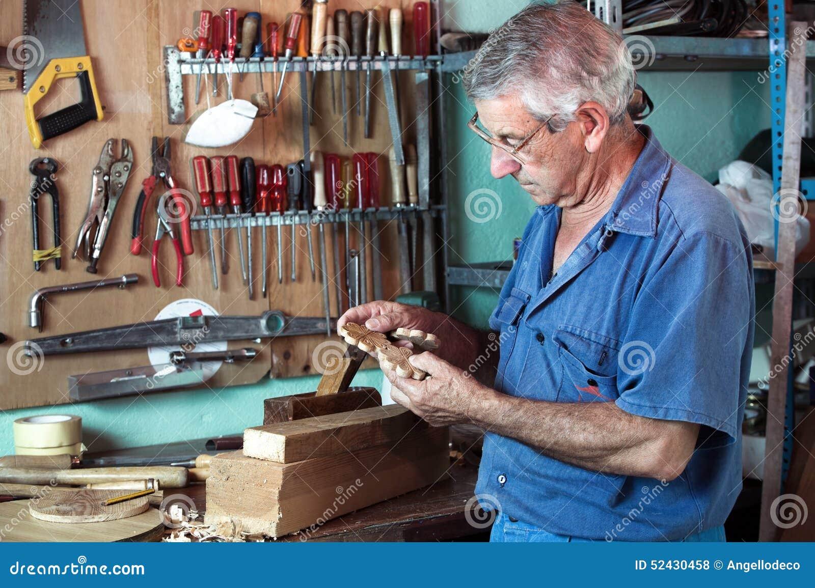 Ο επιπλοποιός εργασίας που κοιτάζει τα ξύλινα κομμάτια στο γκαράζ