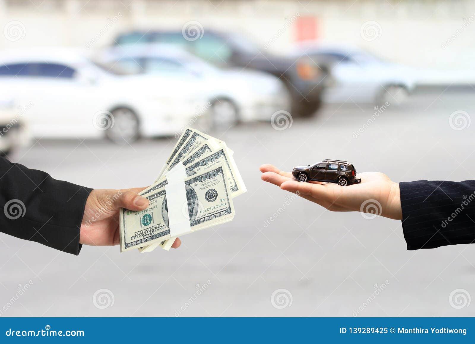 Ο επιχειρηματίας έδωσε τα χρήματα στη επιχειρηματία ή στην πωλήτρια που κρατά τη μικροσκοπική πρότυπη, αυτόματη επιχείρηση αυτοκι