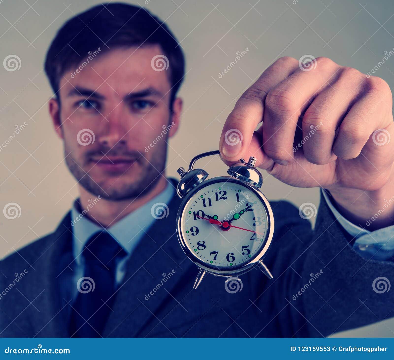 Ο επιχειρηματίας κρατά ένα ξυπνητήρι