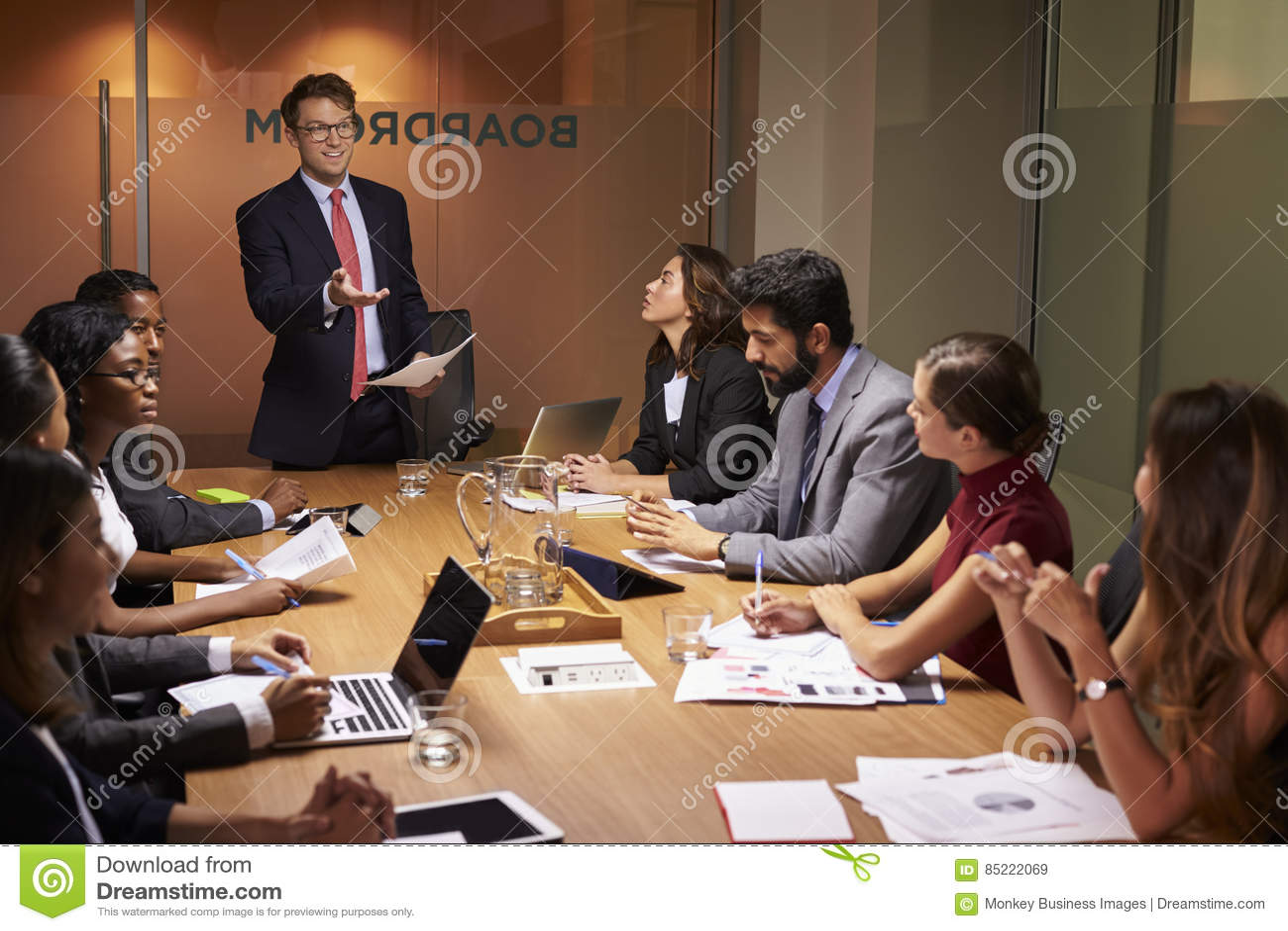 Ο επιχειρηματίας στέκεται στους συναδέλφους σε μια συνεδρίαση