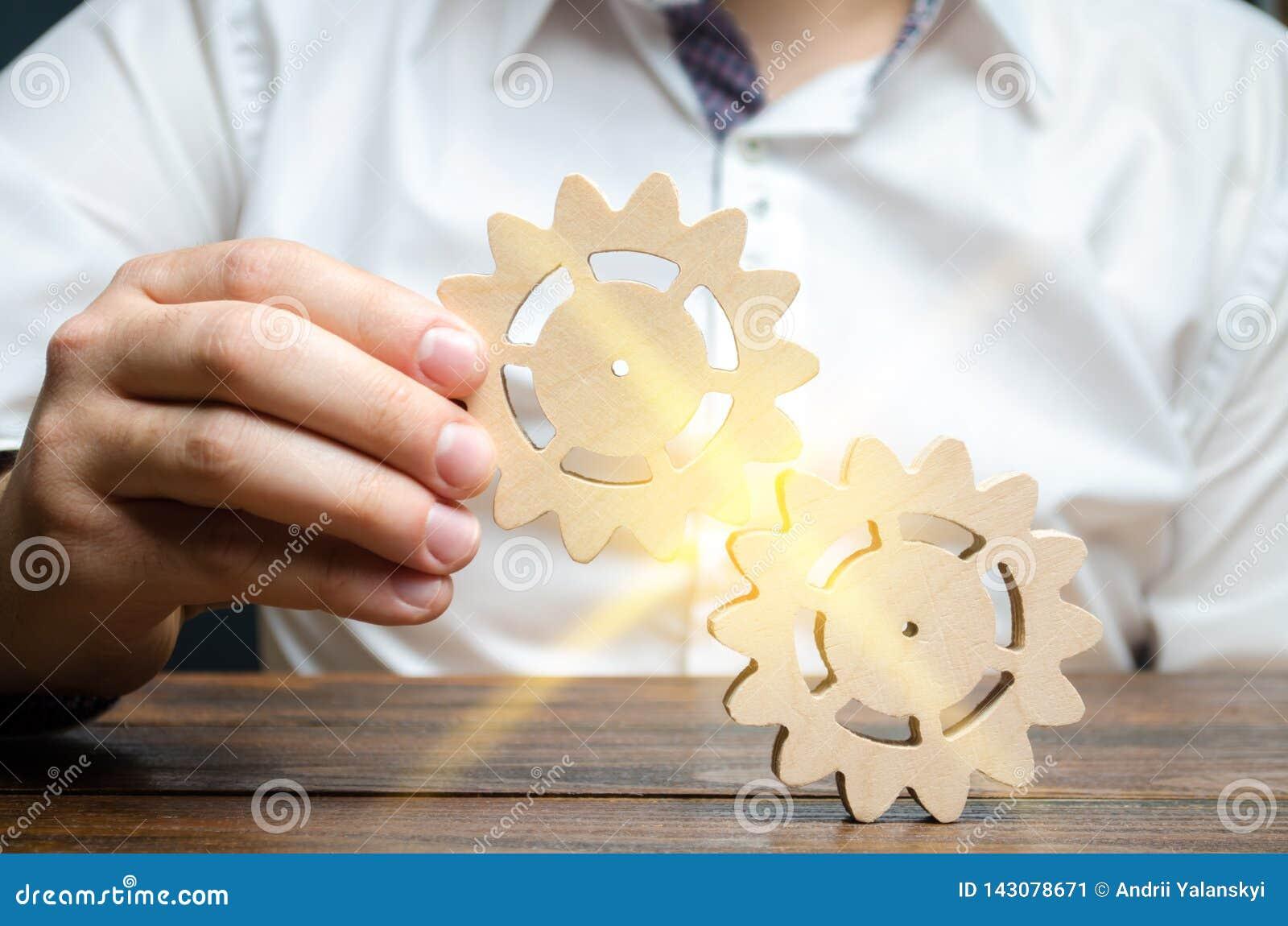 Ο επιχειρηματίας στο άσπρο πουκάμισο συνδέει δύο ξύλινα εργαλεία Συμβολισμός της καθιέρωσης των επιχειρησιακών διαδικασιών και τη