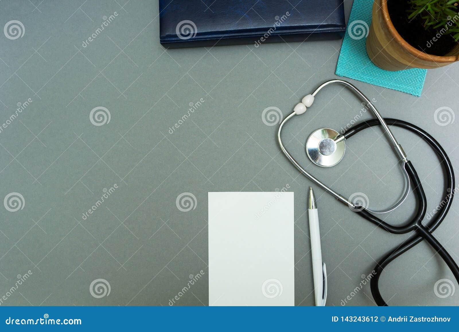 Ο εργασιακός χώρος του γιατρού Σημειωματάριο με τη μάνδρα, το στηθοσκόπιο και flowerpot σε ένα γκρίζο υπόβαθρο