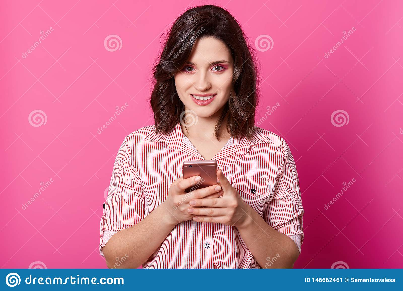 Ο εσωτερικός πυροβολισμός της γοητείας ντυμένο το θηλυκό μοντέρνο πουκάμισο, κρατώντας το smartphone και στα χέρια και εξετάζοντα