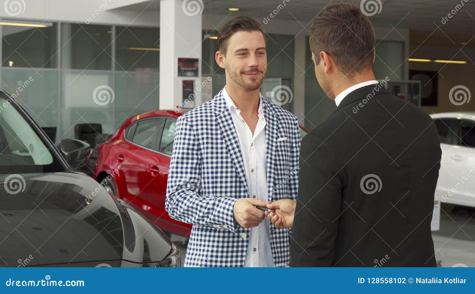 Ο ευτυχής αγοραστής και ο πωλητής κάνουν μια διαπραγμάτευση της αγοράς ενός αυτοκινήτου