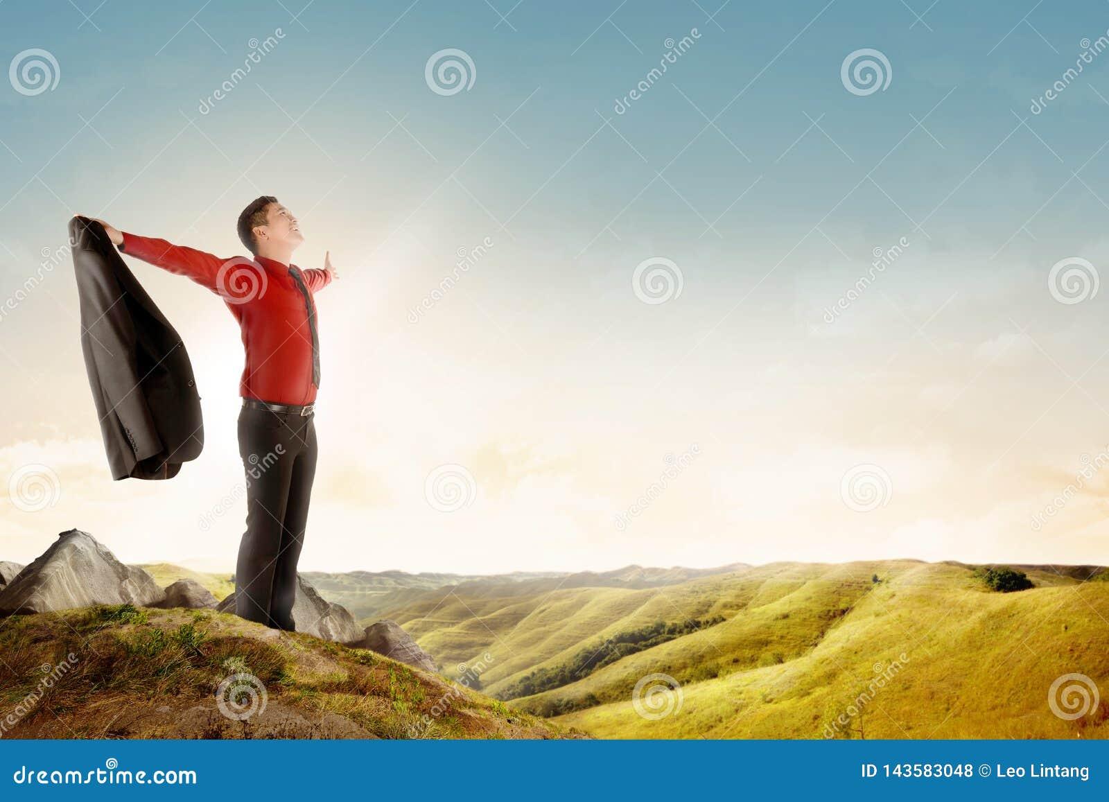 Ο ευτυχής ασιατικός επιχειρηματίας που κρατά ένα κοστούμι στεμένος πάνω από το βουνό γιορτάζει επιτυχή του