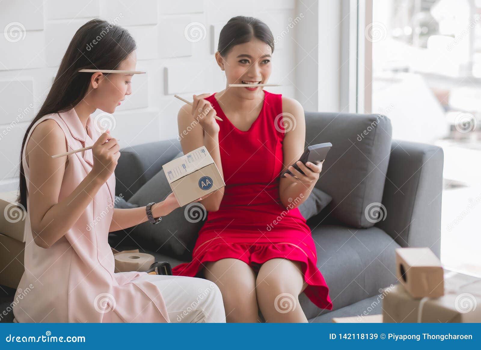 Ο ευτυχής ασιατικός ιδιοκτήτης γυναικών δύο που απασχολείται στο σπίτι στο γραφείο, γυναίκες δημιουργεί τη σε απευθείας σύνδεση,