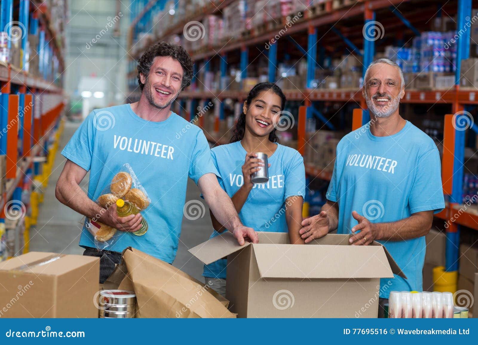 Ο ευτυχής εθελοντής θέτει και χαμογελά κατά τη διάρκεια της εργασίας