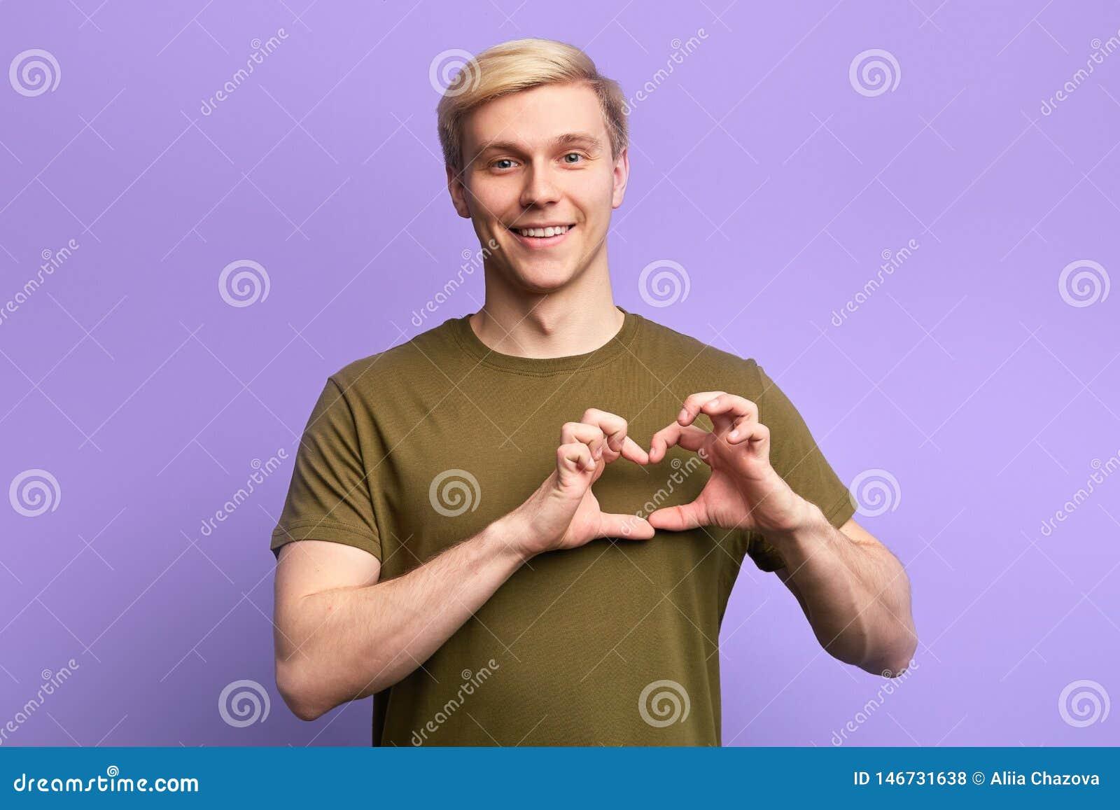 Ο ευτυχής ελκυστικός νεαρός άνδρας, κράτημα παραδίδει τη χειρονομία καρδιών,