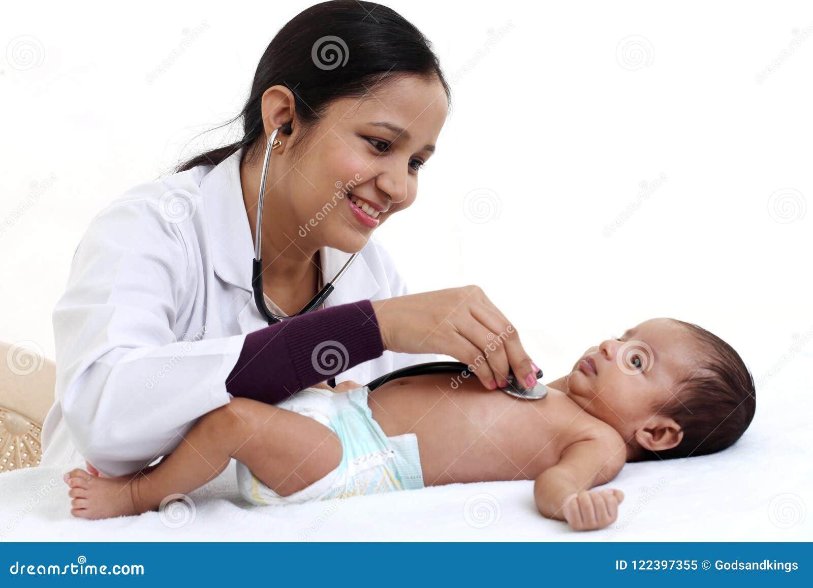 Ο εύθυμος θηλυκός παιδίατρος κρατά το νεογέννητο μωρό