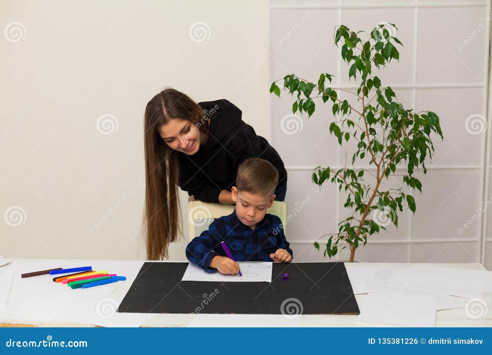 Ο θηλυκός δάσκαλος διδάσκει ένα μικρό αγόρι για να σύρει στον πίνακα
