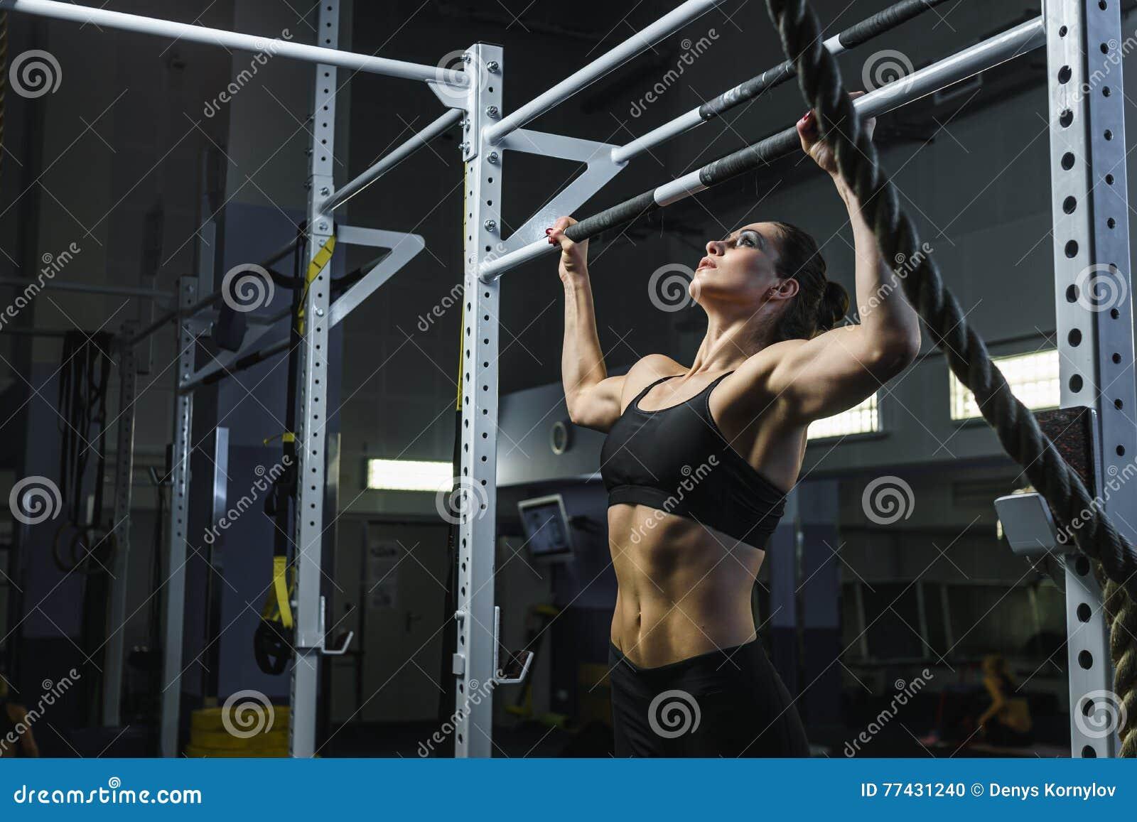 Ο ισχυρός ελκυστικός εκπαιδευτής CrossFit γυναικών τραβά το UPS κατά τη διάρκεια του workout