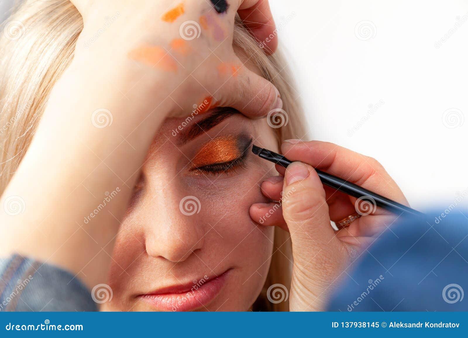 Ο καλλιτέχνης Makeup με μια βούρτσα στα χέρια με μια επίπεδη άκρη χρωματίζει το βέλος στο βλέφαρο του προτύπου, εφαρμόζει τη σύνθ