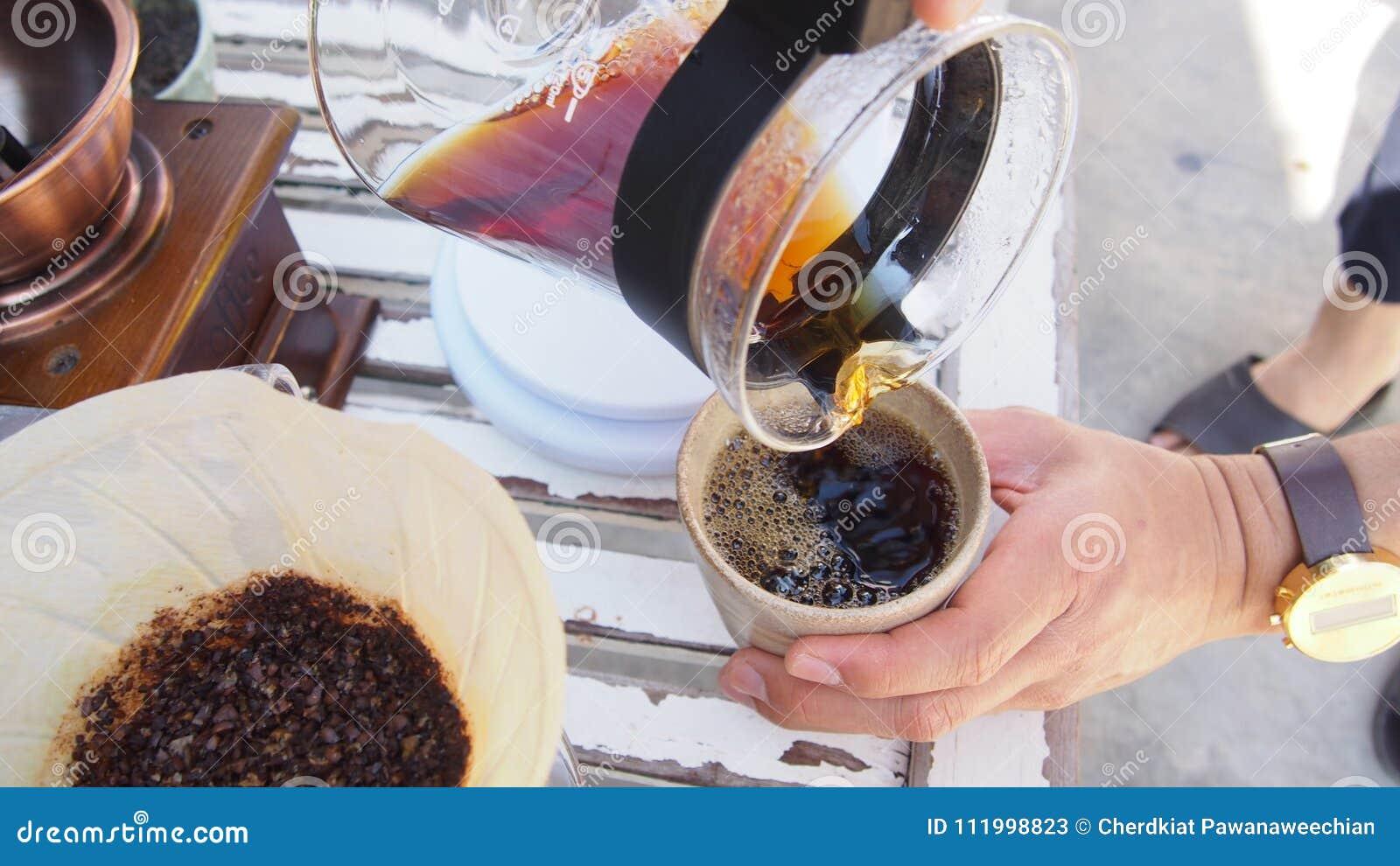 Ο καφές σταλαγματιάς χεριών, χύνοντας ζεστό νερό Barista πέρα από ψημένος η σκόνη καφέ κάνοντας τη σταλαγματιά να παρασκευάσει το