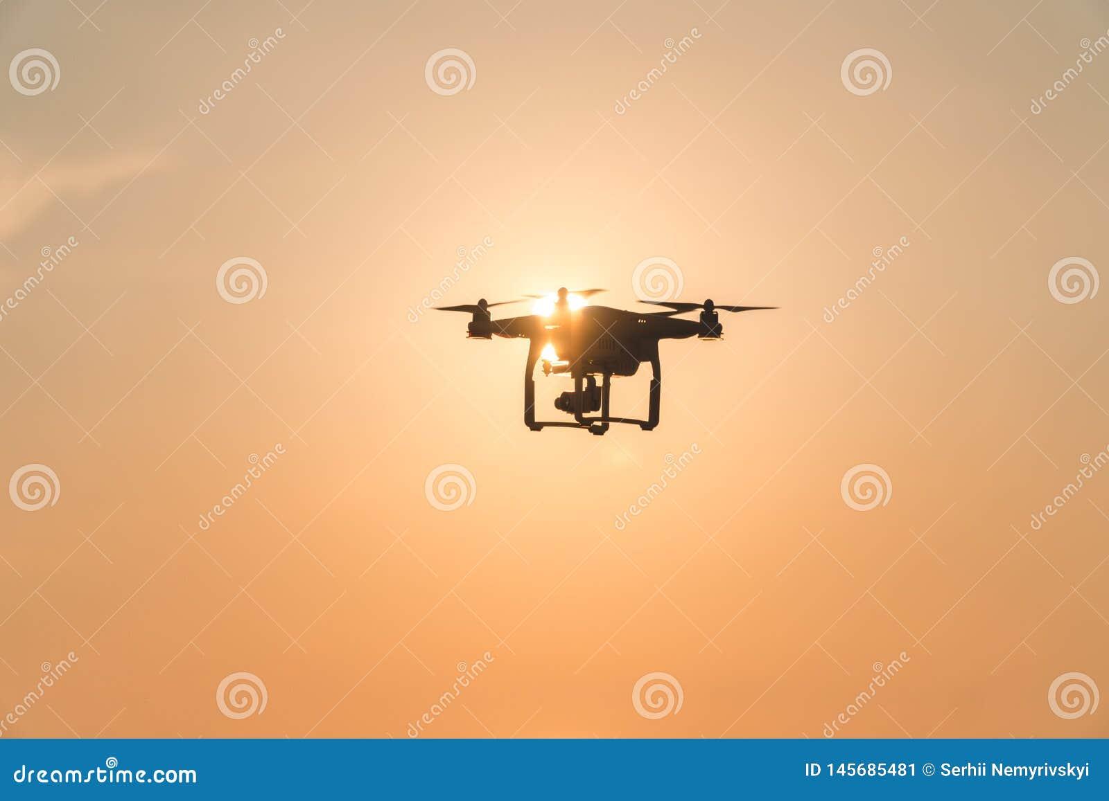 Ο κηφήνας στον ουρανό ηλιοβασιλέματος τα ωκεάνια βουνά κυμάτων κλείνουν επάνω του quadrocopter υπαίθρια έννοια για γαμήλιο videog
