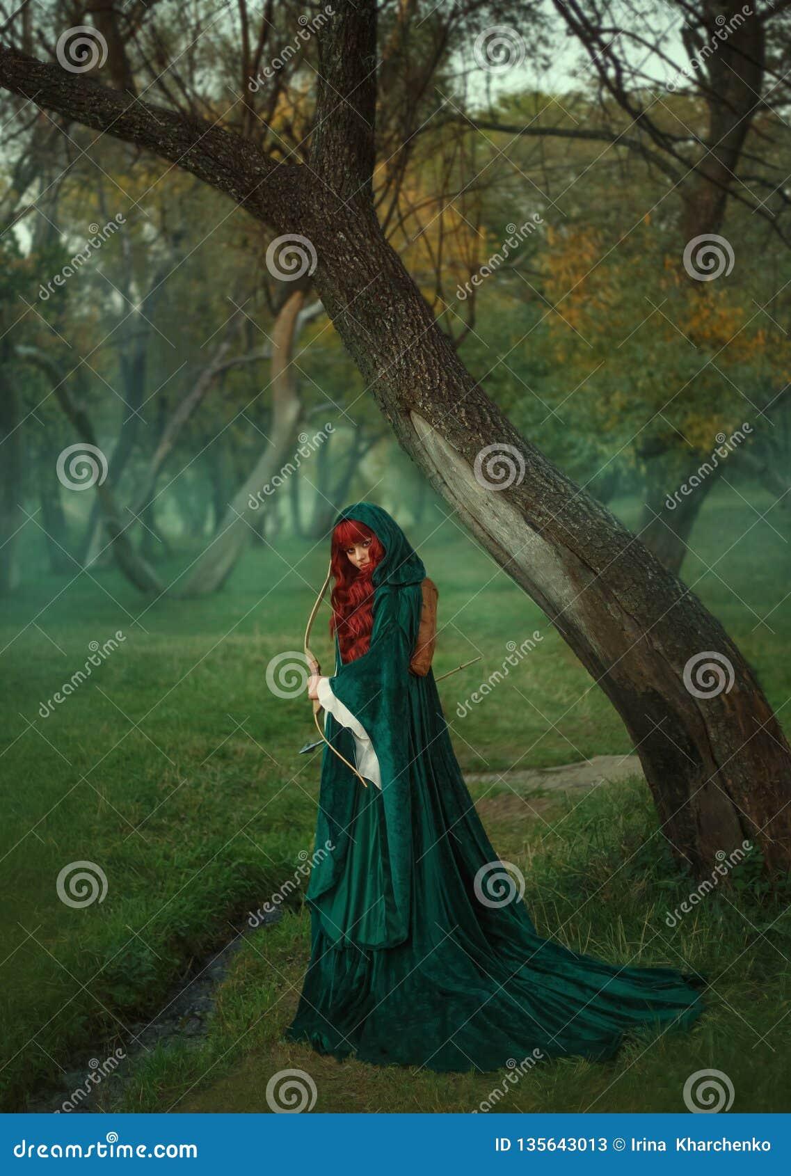 Ο κυνηγός, κοκκινομάλλες κορίτσι με ένα τόξο παραδίδει μέσα την αναζήτηση του θύματος, που ντύνεται στο πράσινα σμαραγδένια φόρεμ