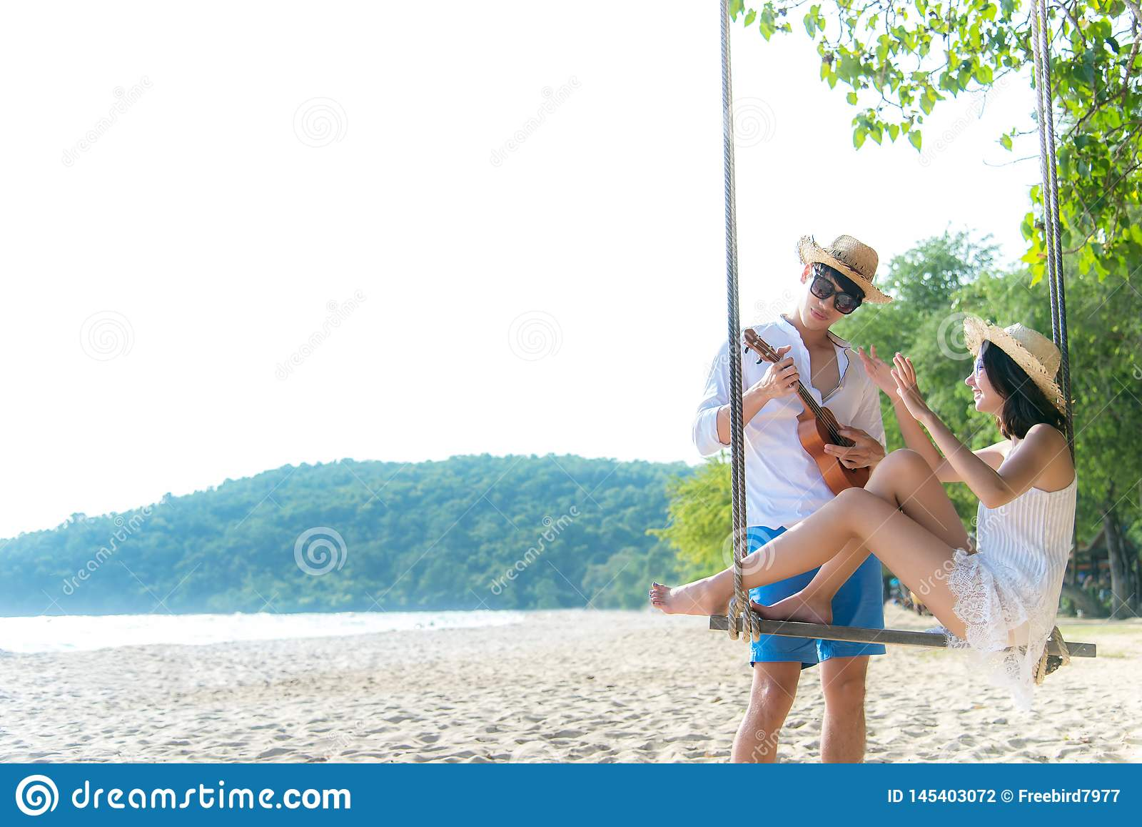 Το ασιατικό ρομαντικό ζεύγος κάθεται στην παραλία θάλασσας στην ταλάντευση σχοινιών χαλαρώνει και ευτυχία για τις διακοπές Ο μήνα