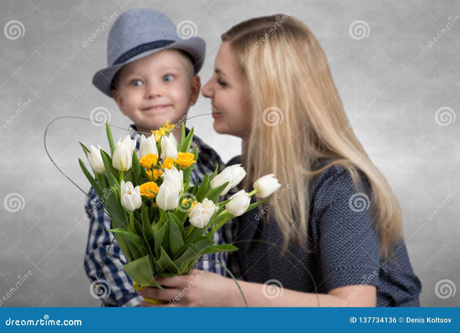 Ο μικρός γιος δίνει στην αγαπημένη μητέρα του μια ανθοδέσμη των όμορφων τουλιπών Άνοιξη, έννοια των οικογενειακών διακοπών Ανθοδέ