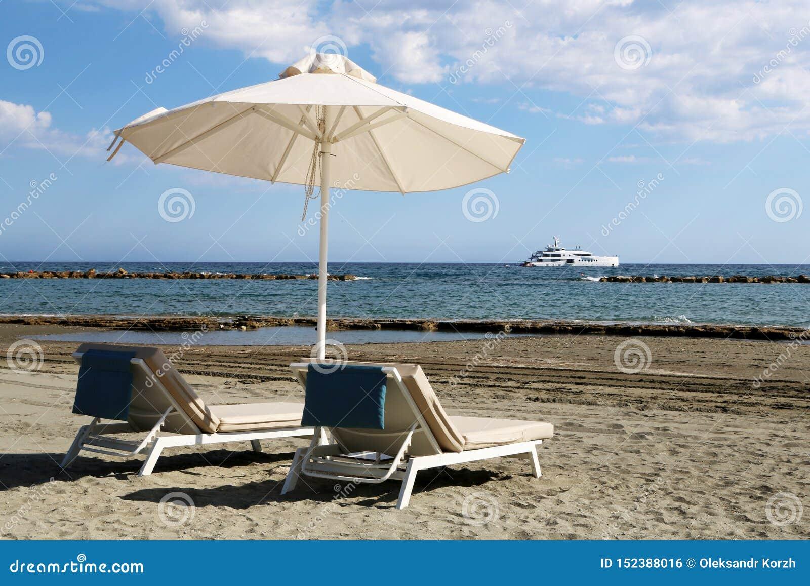 Ο μοντέρνος αργόσχολος στην κίτρινη άμμο στον ήλιο στην παραλία