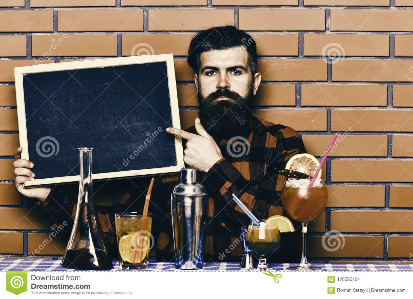 Ο μπάρμαν, bartender ή hipster κρατά τη διαφήμιση φραγμών Έννοια επιλογών φραγμών Ο μπάρμαν με τη γενειάδα και το σοβαρό πρόσωπο