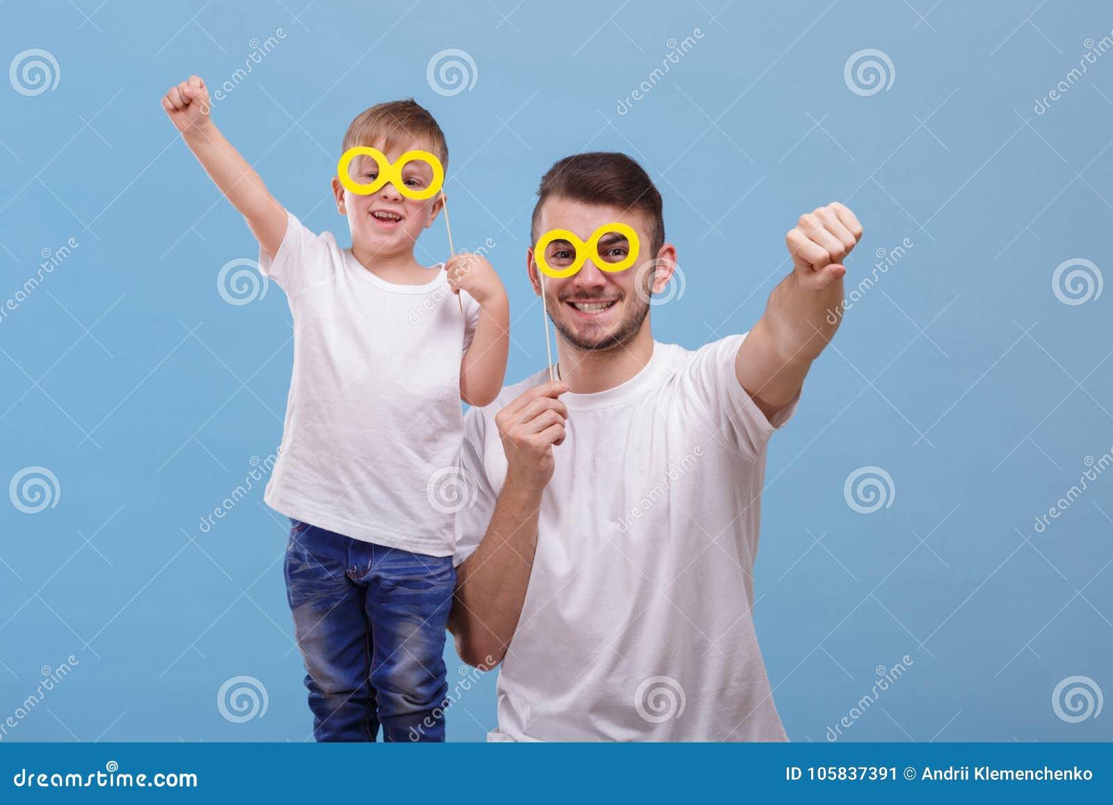 Ο μπαμπάς και ο γιος του βάζουν τα γυαλιά τους σε ένα ραβδί σε ένα μπλε υπόβαθρο