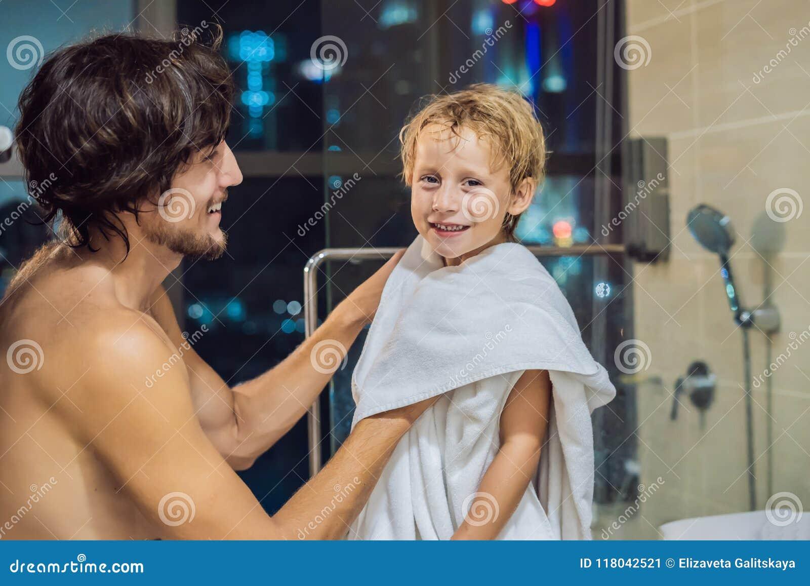 Ο μπαμπάς σκουπίζει το γιο του με μια πετσέτα μετά από ένα ντους στο BEF βραδιού