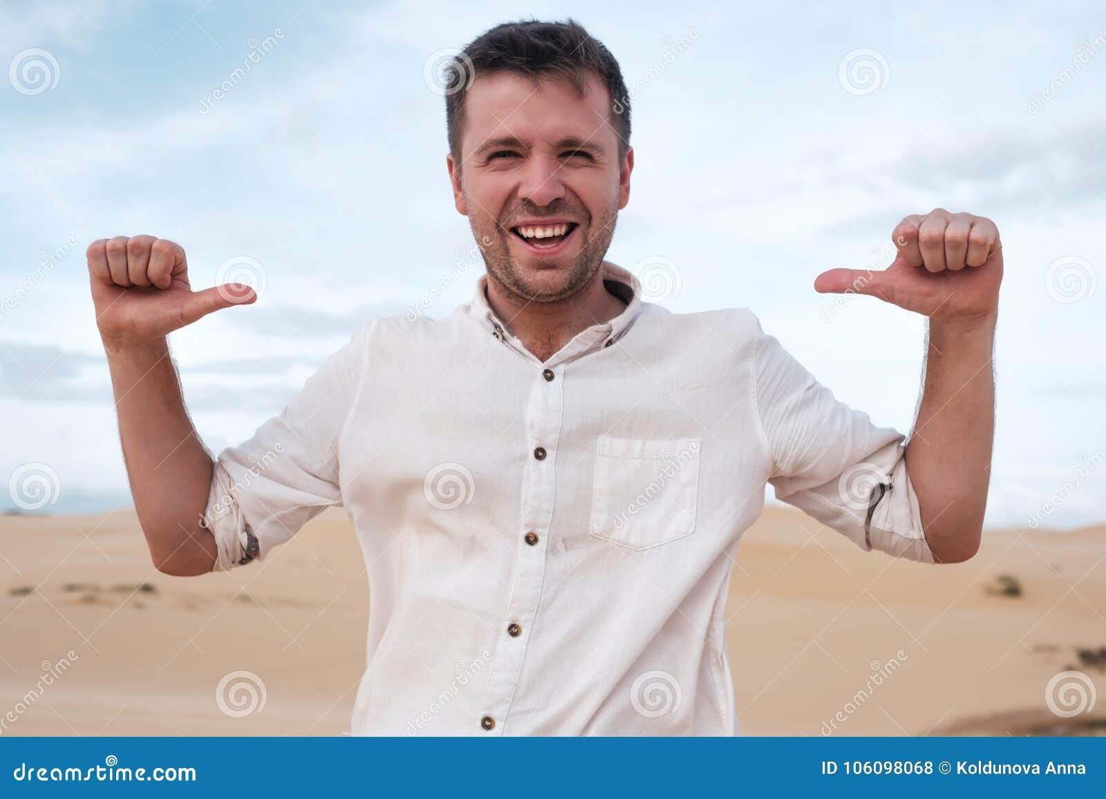 Ο μόνος-ικανοποιώντας και υπερήφανος καυκάσιος νεαρός άνδρας φαίνεται προς τα εμπρός παρουσιάζοντας με τους αντίχειρες σε τον