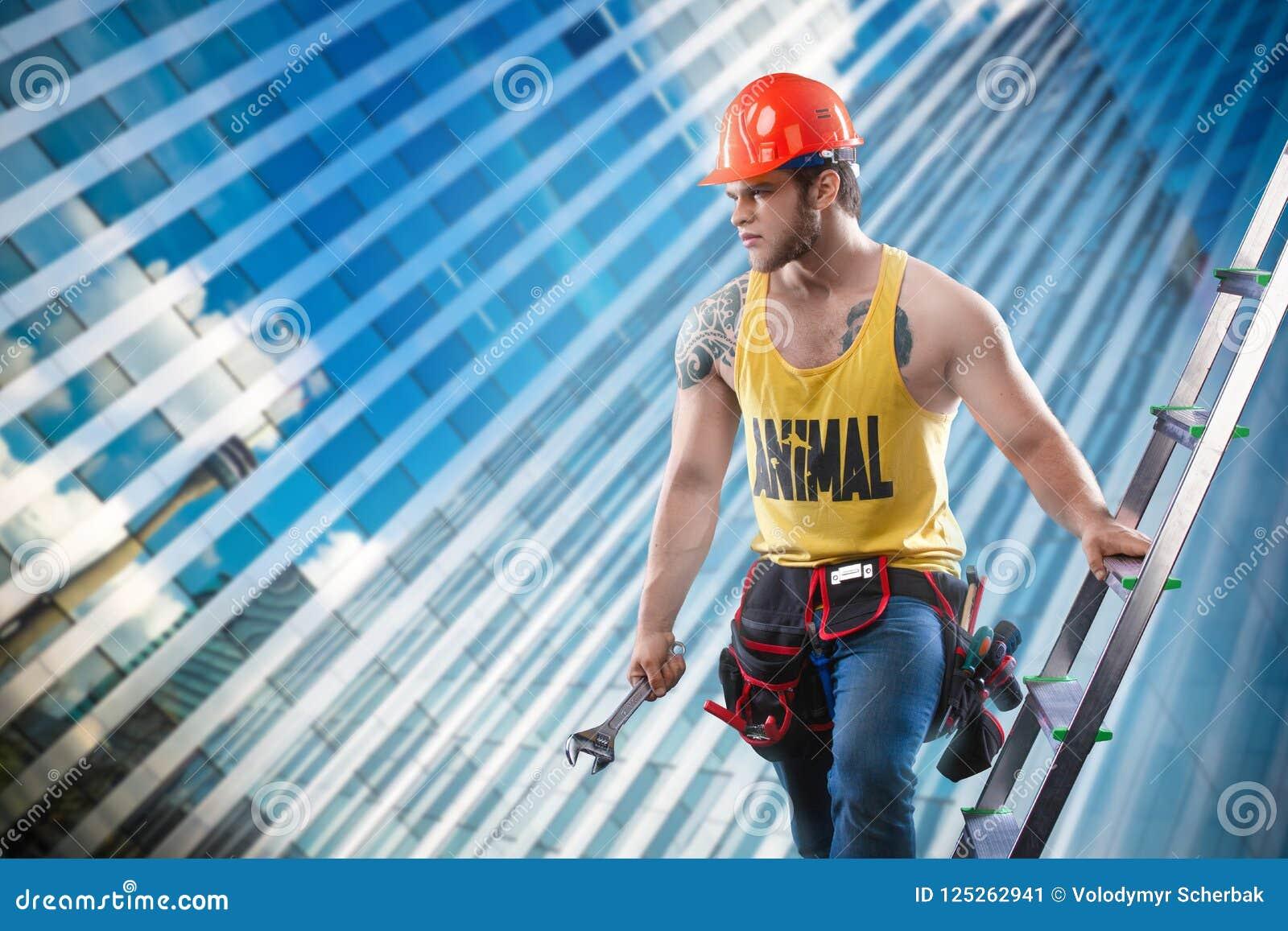 Ο νέος όμορφος οικοδόμος ατόμων φαλλοκρατών με το προκλητικό μυϊκό αθλητικό ισχυρό σώμα στο πορτοκαλί σκληρό καπέλο ή το κράνος κ