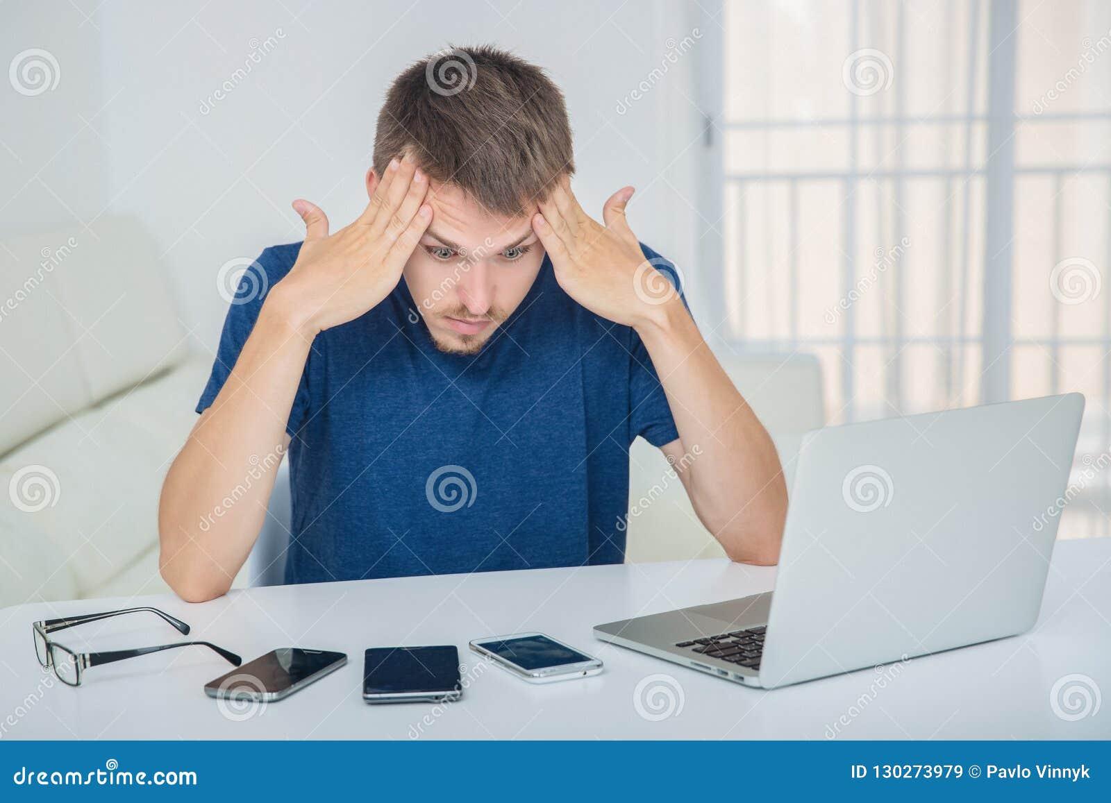 Ο νεαρός άνδρας έχει έναν πονοκέφαλο από τον υψηλό φόρτο εργασίας