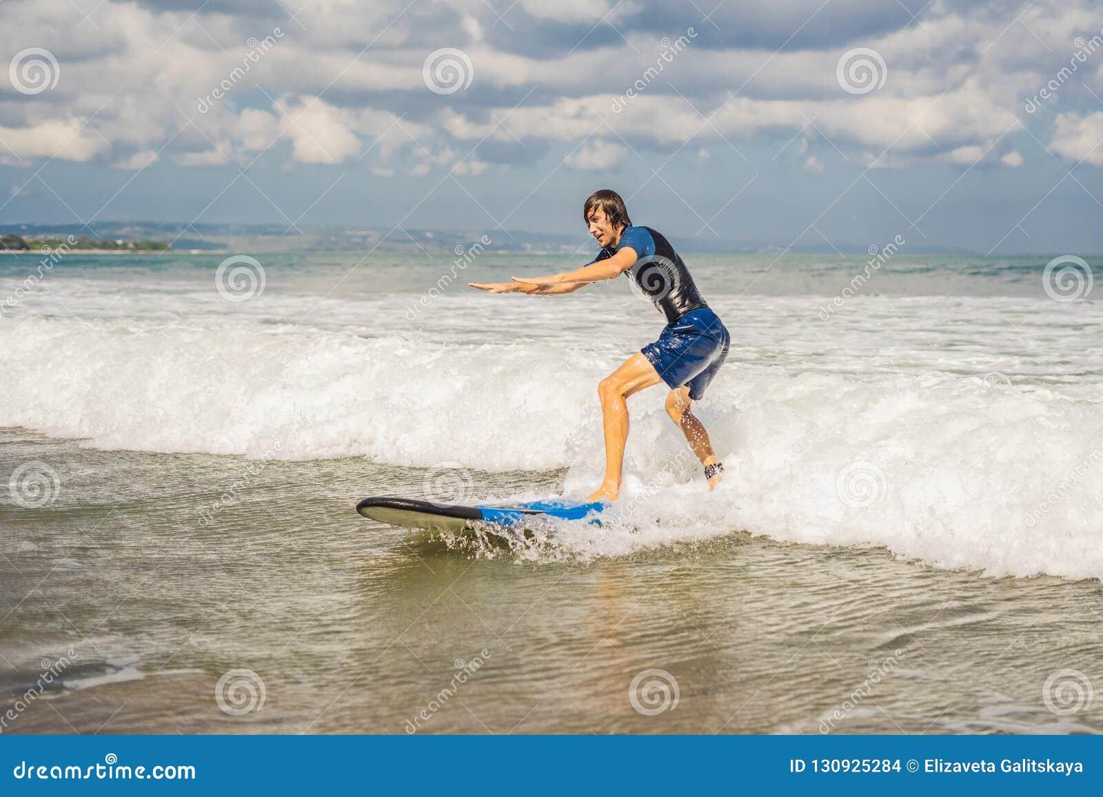 Ο νεαρός άνδρας, αρχάριος Surfer μαθαίνει να κάνει σερφ σε έναν αφρό θάλασσας στο Β
