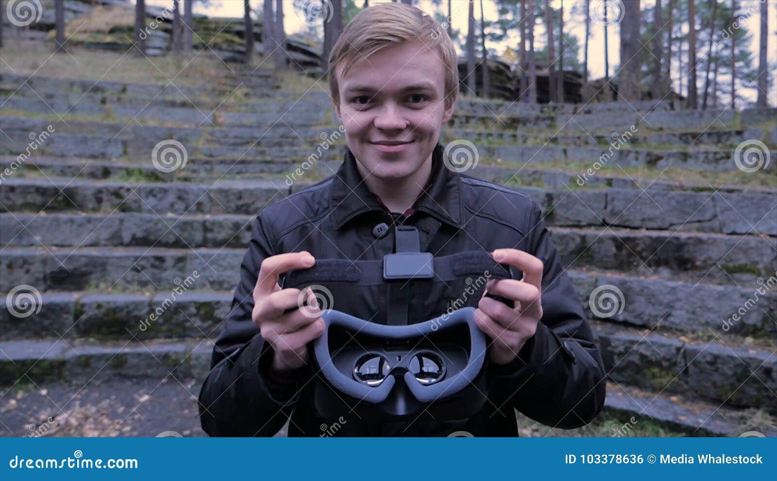 Ο νεαρός άνδρας δίνει μια κάσκα εικονικής πραγματικότητας στο πάρκο Ο νεαρός άνδρας δίνει μια κάσκα εικονικής πραγματικότητας στο