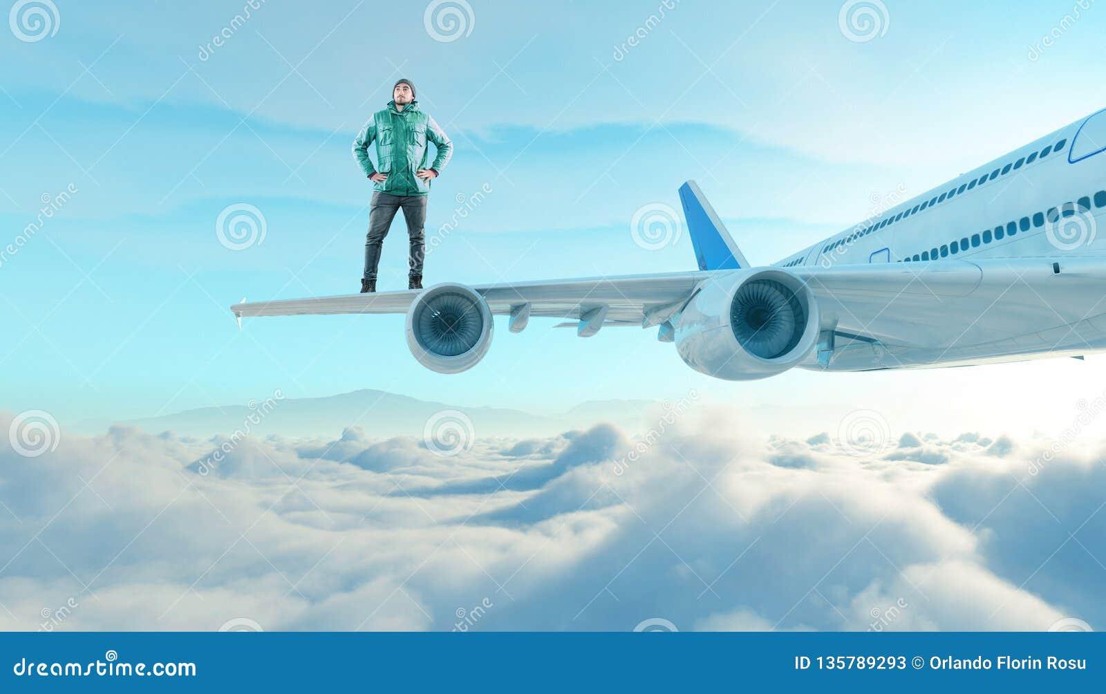 Ο νεαρός άνδρας στέκεται στο φτερό ενός αεροπλάνου